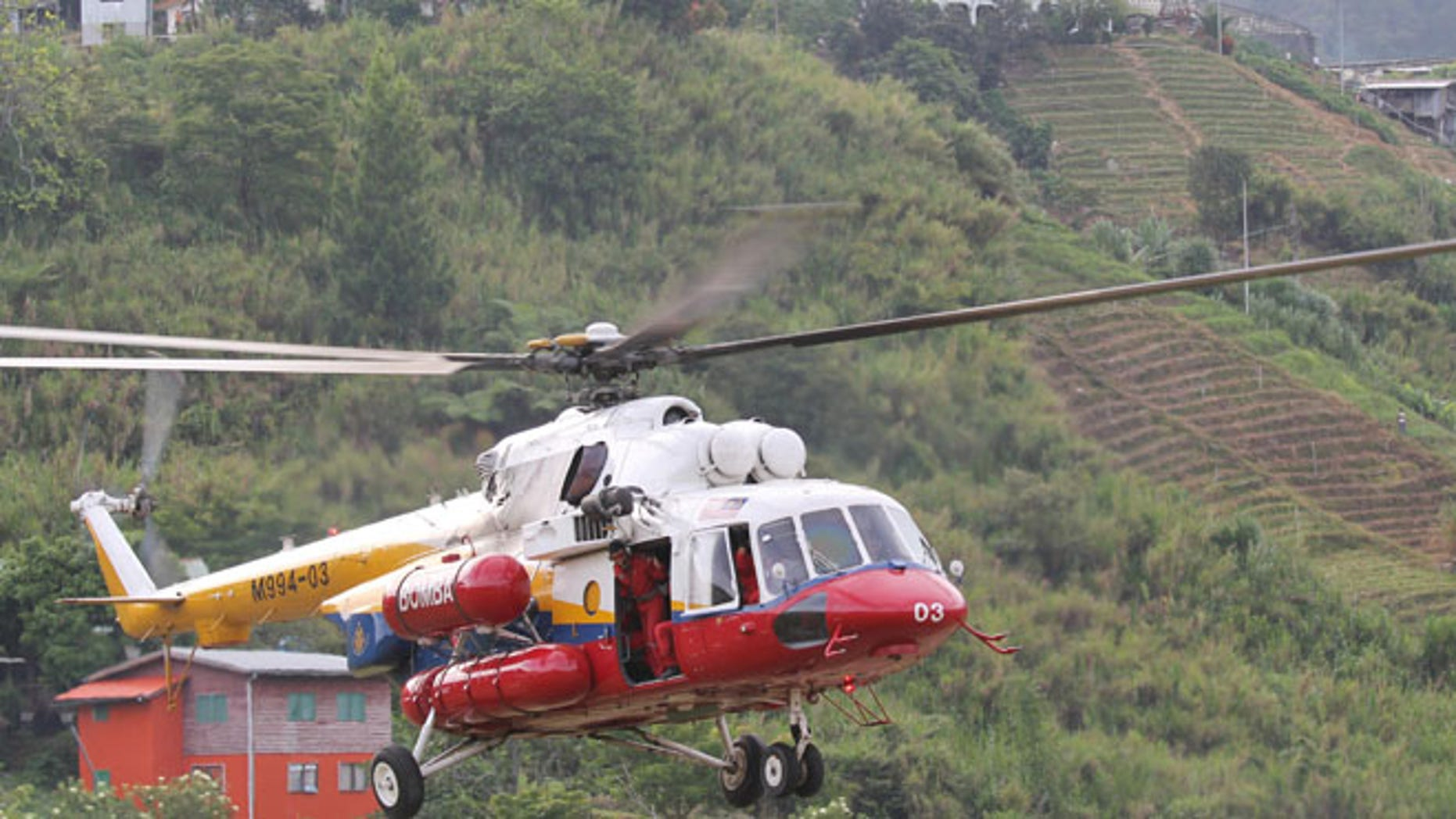 June 6, 2015:A helicopter leaves Kundasang, Malaysia for Mount Kinabalu to recover the bodies of climbers. (AP)