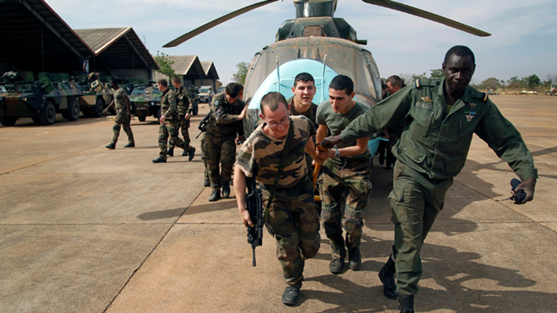 Jan. 15. 2013: Malian soldiers helped by French troops, move a broken helicopter out a hangar to make room for more incoming troops  at Bamako's airport.