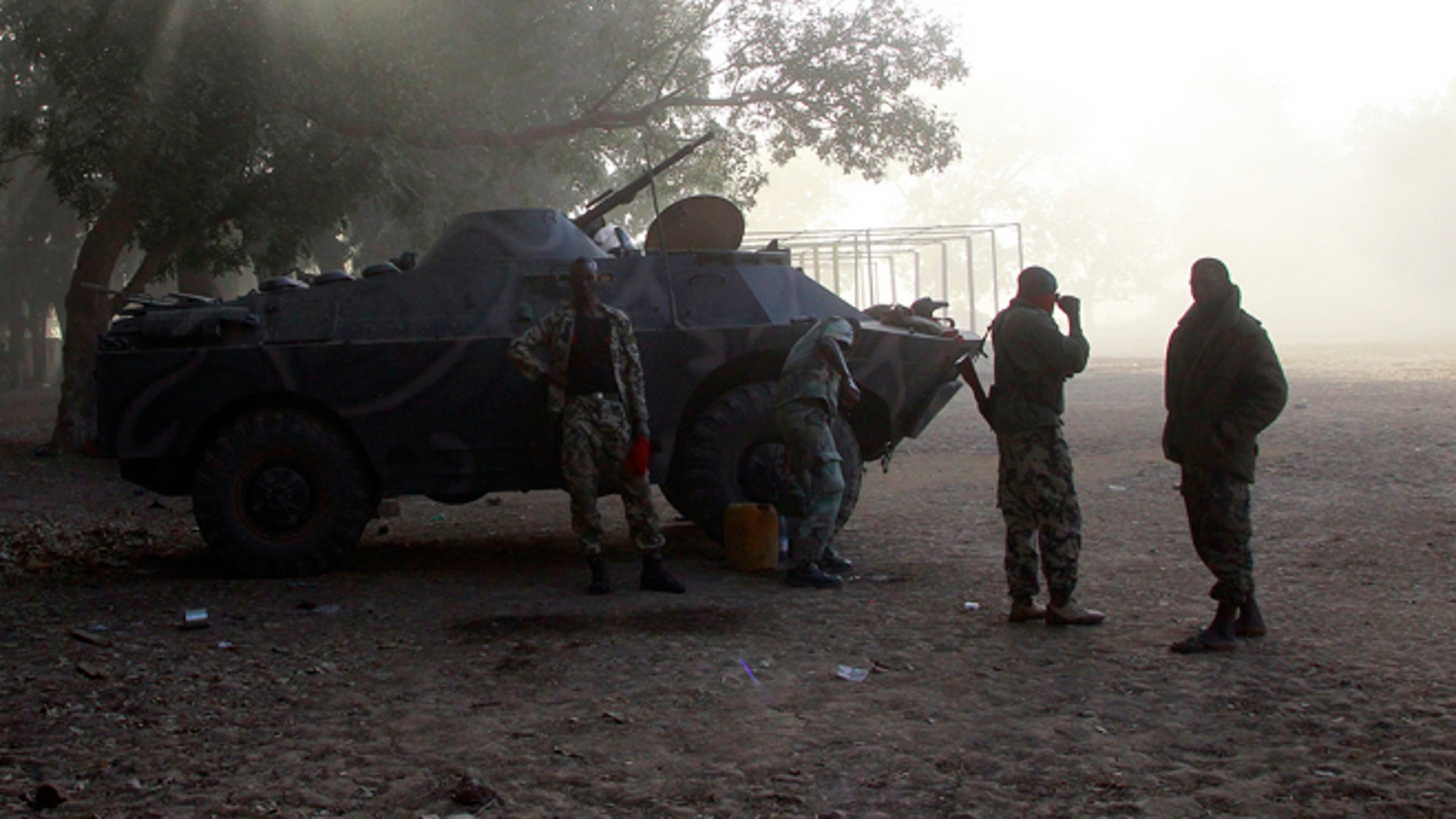 Jan. 20, 2013: Malian soldiers stand by their APC as a French Puma transport helicopter lands to test the field in the center of  Niono, some  400 kms (300 miles) North of the capital Bamako.