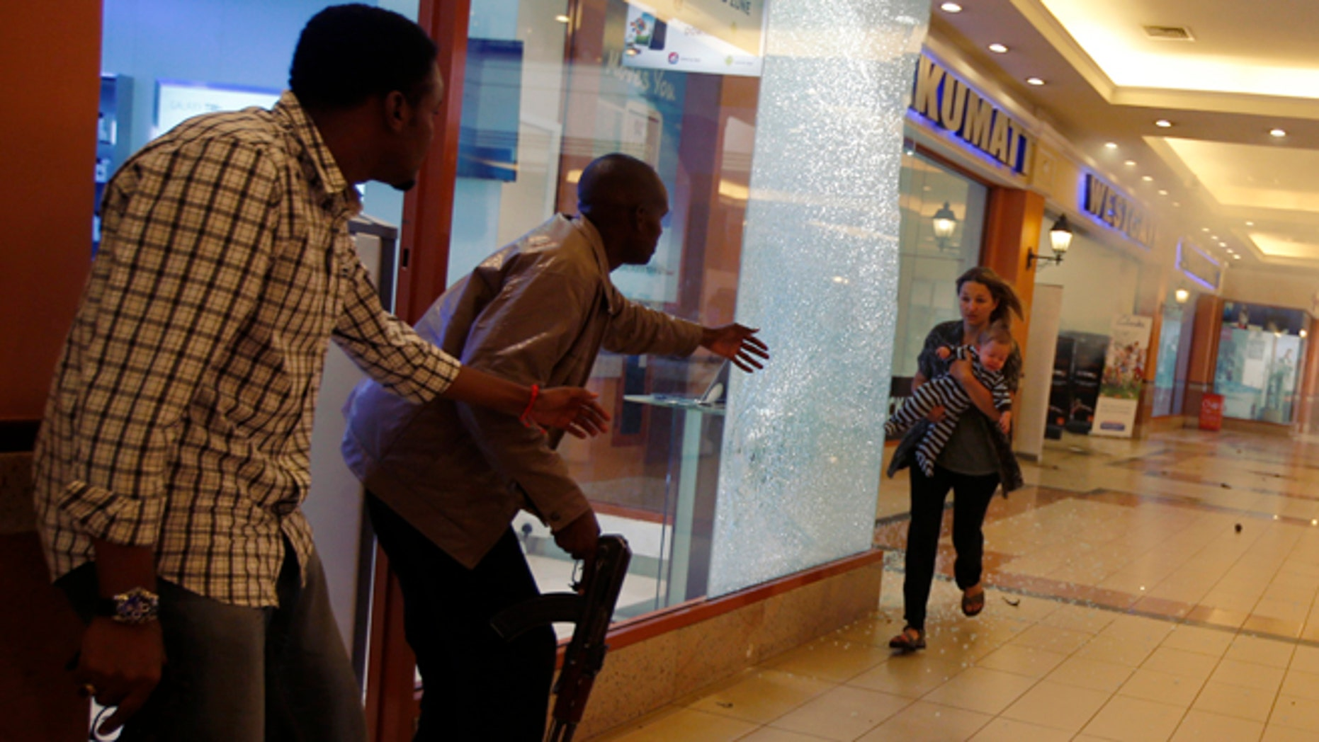 Armed police guide a woman carrying a child to safety as they hunt gunmen who went on a shooting spree at Westgate shopping centre in Nairobi, September 21, 2013.