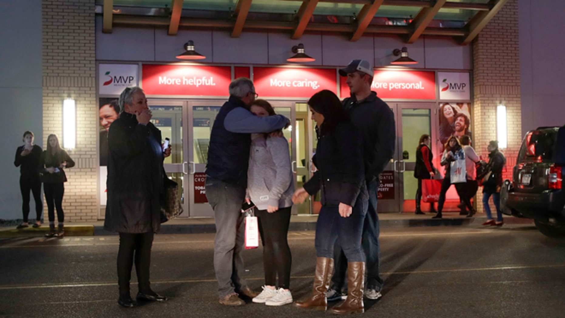 People embrace after leaving Crossgates Mall in Guilderland, N.Y., after reports of gunfire inside, Saturday, Nov. 12, 2016. The Albany Times-Union says hundreds of people were evacuated and the mall was locked down. (AP Photo/Michael Groll)