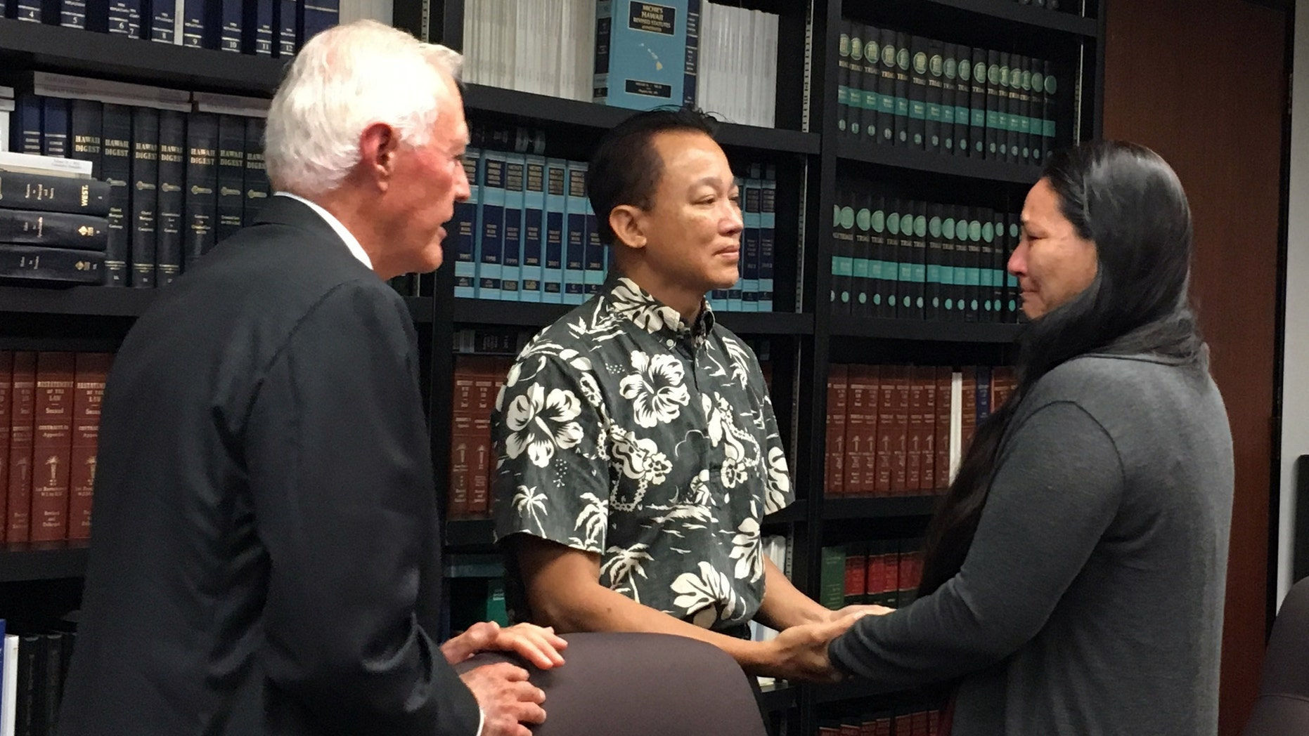 Keith Lee, center, a lawyer representing the Waianae Coast Health Center, holds hands with Rachel Marrero as her attorney Richard Fried looks on at a news conference in Honolulu, Wednesday, Sept. 14, 2016. The federal government is settling her malpractice lawsuit for $4.2 million after her husband went to the Waianae Coast Comprehensive Health Center with a sore throat and ended up dead. (AP Photo/Jennifer Sinco)