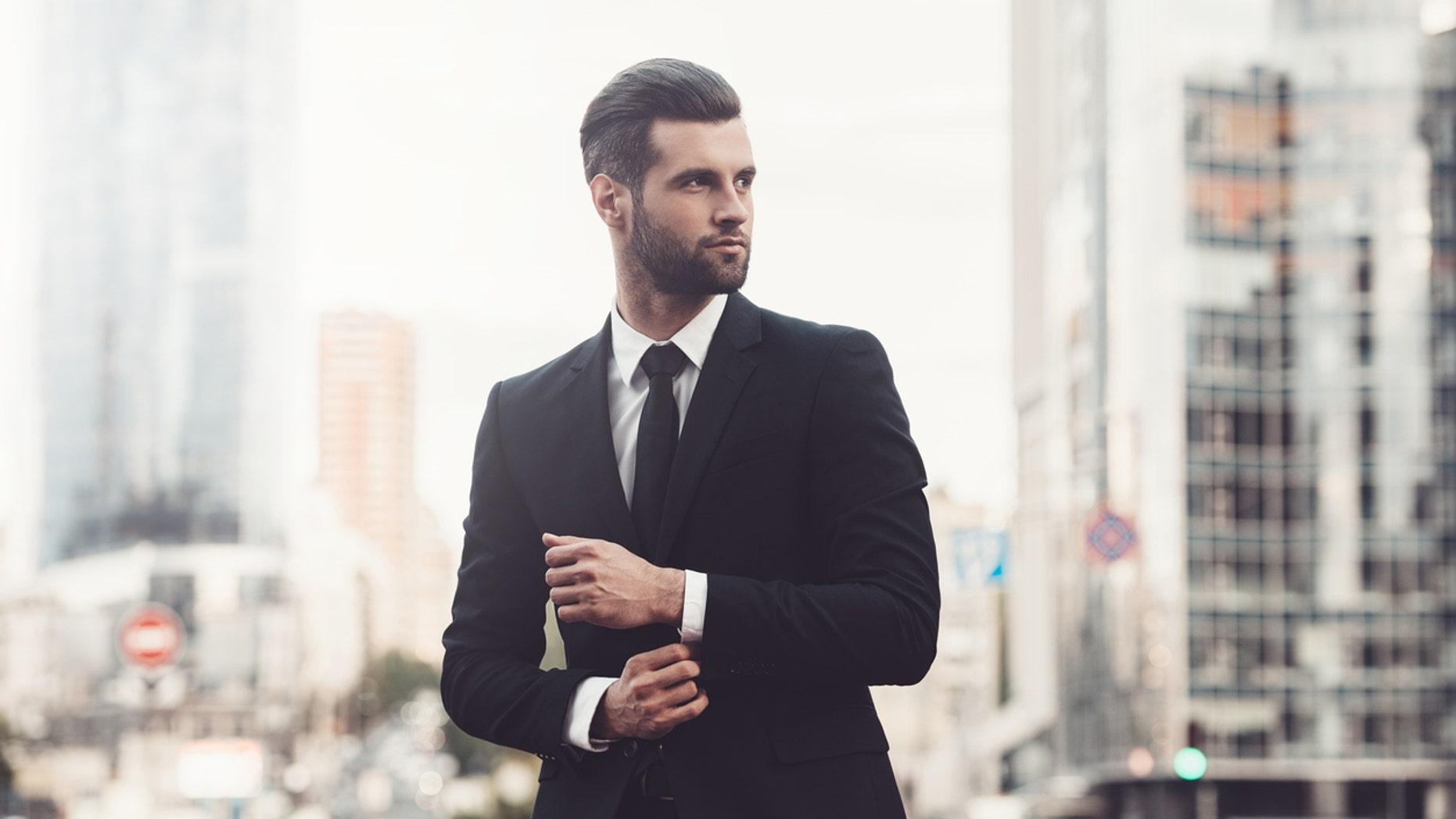 Confident young man in full suit adjusting his sleeve and looking away while standing outdoors with cityscape in the background
