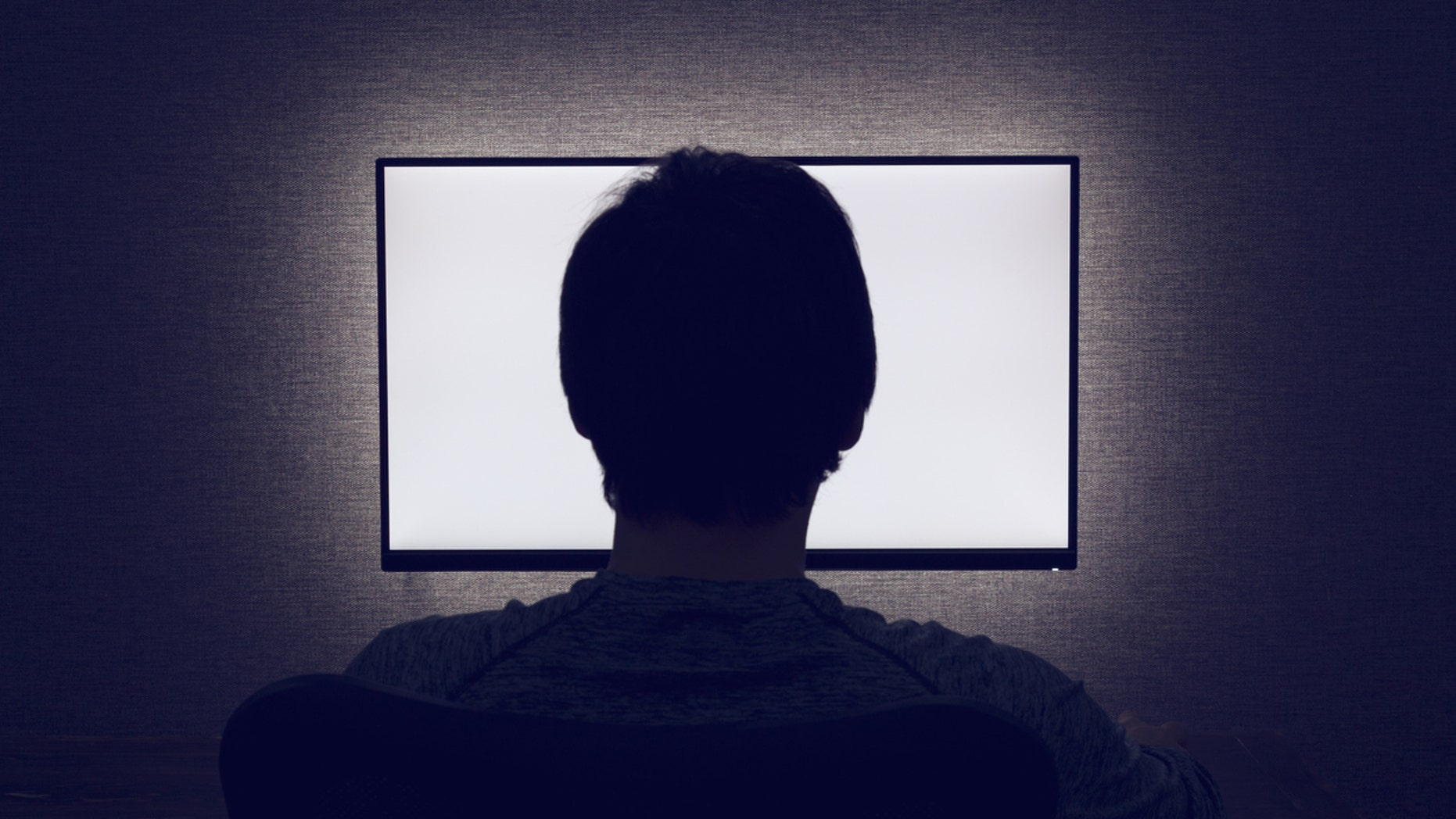 Man sits in front of a blank monitor in dark room