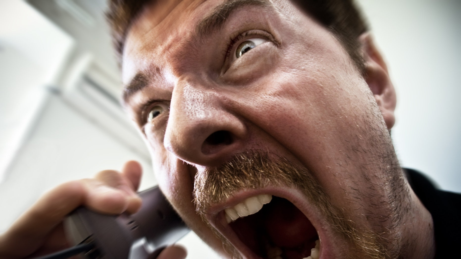 Extreme angry man shouting at the phone
