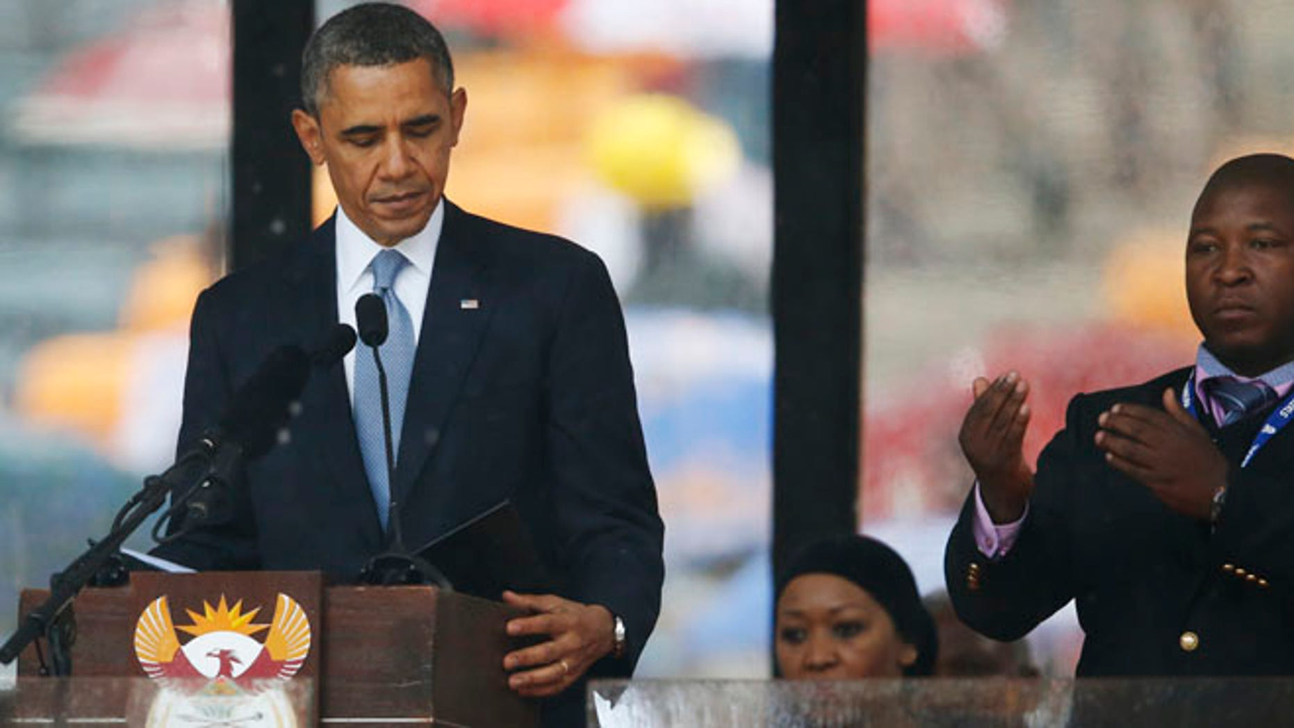 """Dec. 10, 2013: President Barack Obama looks down as he stands next to the sign language interpreter as he makes his speech at the memorial service for former South African president Nelson Mandela at the FNB Stadium in Soweto near Johannesburg.  South Africa's deaf federation said on Wednesday that the interpreter on stage for Mandela memorial was a """"fake."""" (AP)"""