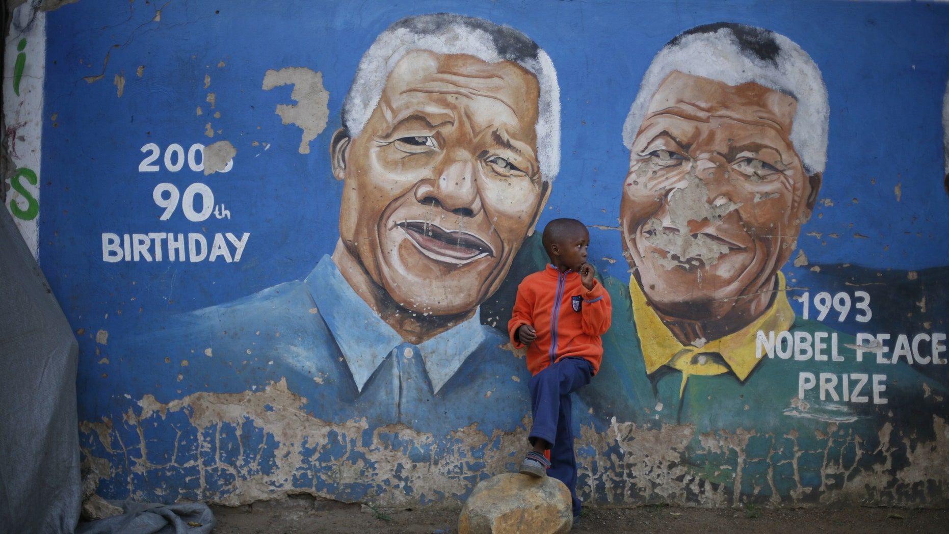 "Hussein Gallo, 7, stands by a mural of Nelson Mandela in the Soweto township in Johannesburg, South Africa, Saturday June 7 2013. Former South African President Nelson Mandela is in ""serious but stable"" condition after being taken to a hospital to be treated for a lung infection, the government said Saturday, prompting an outpouring of concern from admirers of a man who helped to end white racist rule. (AP Photo/Jerome Delay)"