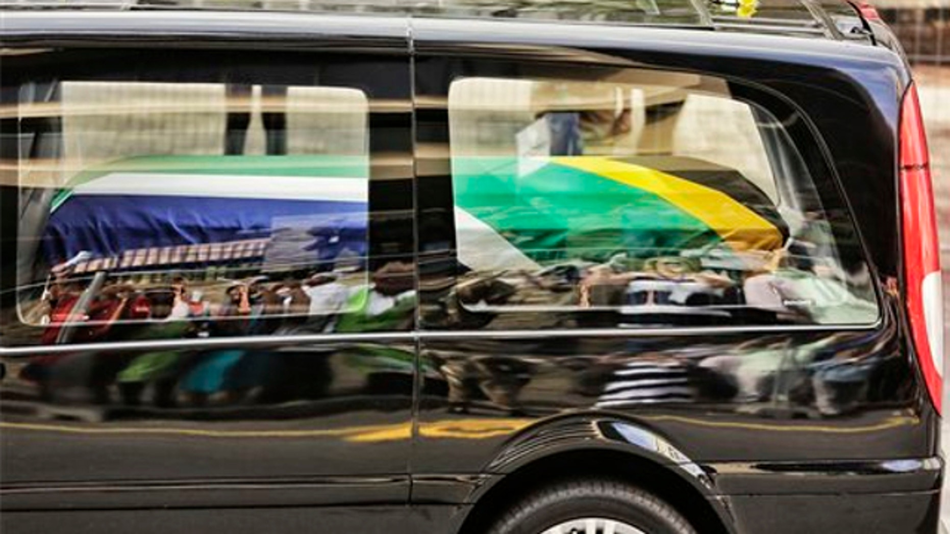 Dec. 11, 2013: People are reflected in the car carrying former South African president Nelson Mandela as it makes its way through the streets of Pretoria, South Africa.