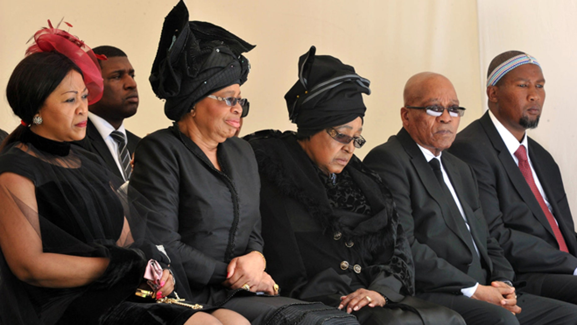 Dec. 15, 2013: From left: Tobeka Zuma, Nelson Mandelas widow Graca Machel, Winnie Madikizela-Mandela, Nelson Mandela's former wife, South African President Jacob Zuma, and Mandela's grandson Mandla Mandela watch as former South African President Nelson Mandela's casket arrives at his burial site following his funeral service in Qunu, South Africa.