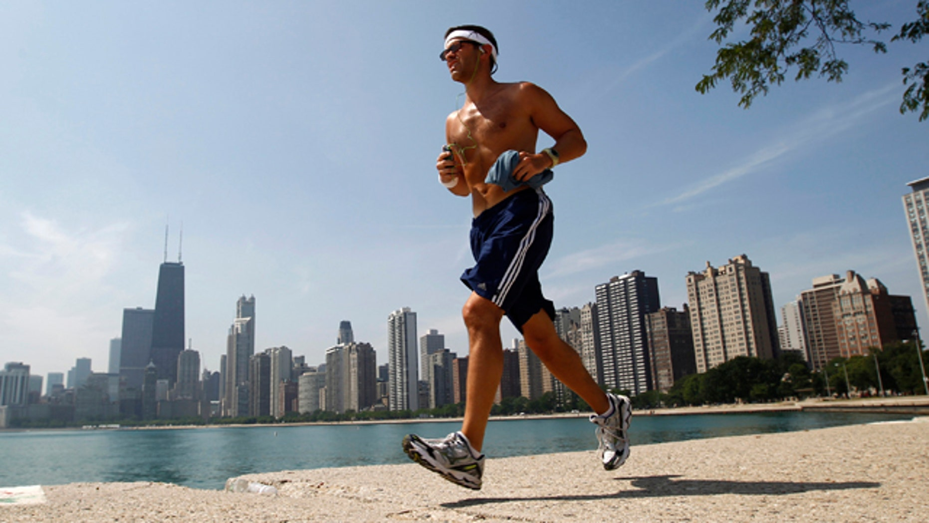 A man runs along the water near North Avenue Beach in Chicago July 20, 2011. The heat index is expected to exceed 110 degrees Fahrenheit or 43 degrees Celsius. REUTERS/Jim Young (UNITED STATES - Tags: ENVIRONMENT)