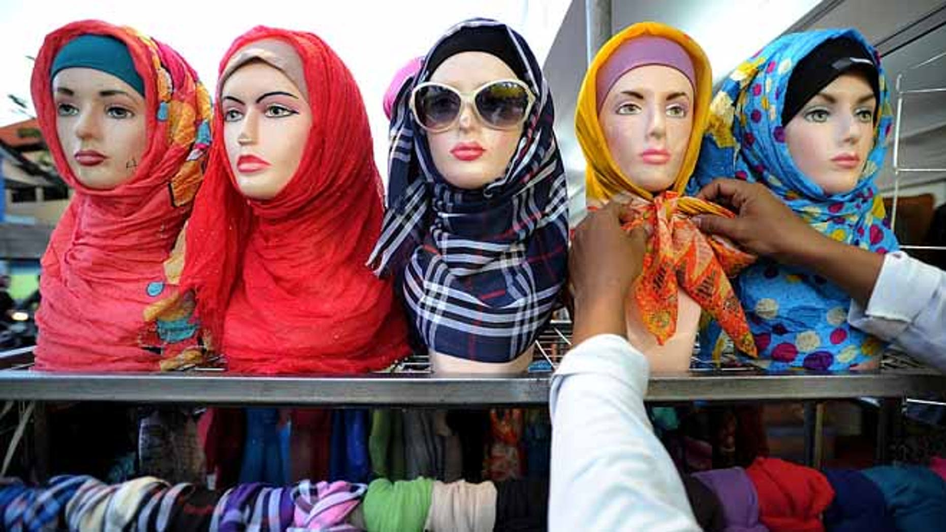 SURABAYA, INDONESIA - JUNE 17:  A vendor prepares hijabs for sale during Ramadan on June 17, 2015 in Surabaya, Indonesia. Muslims worldwide observe Ramadan, the ninth month of the Islamic calendar which is marked by a holy month of fasting, prayer, and recitation of the Quran.  (Photo by Robertus Pudyanto/Getty Images)
