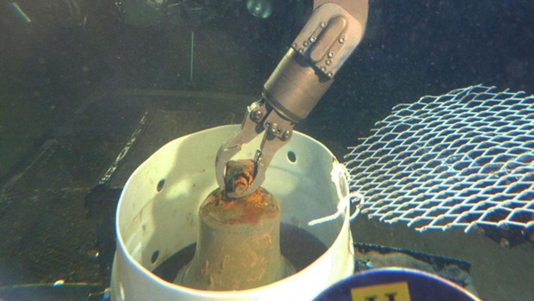 Manipulator arm of HURL's submersible places the I-400 bell into a collection basket. (HURL/UH)