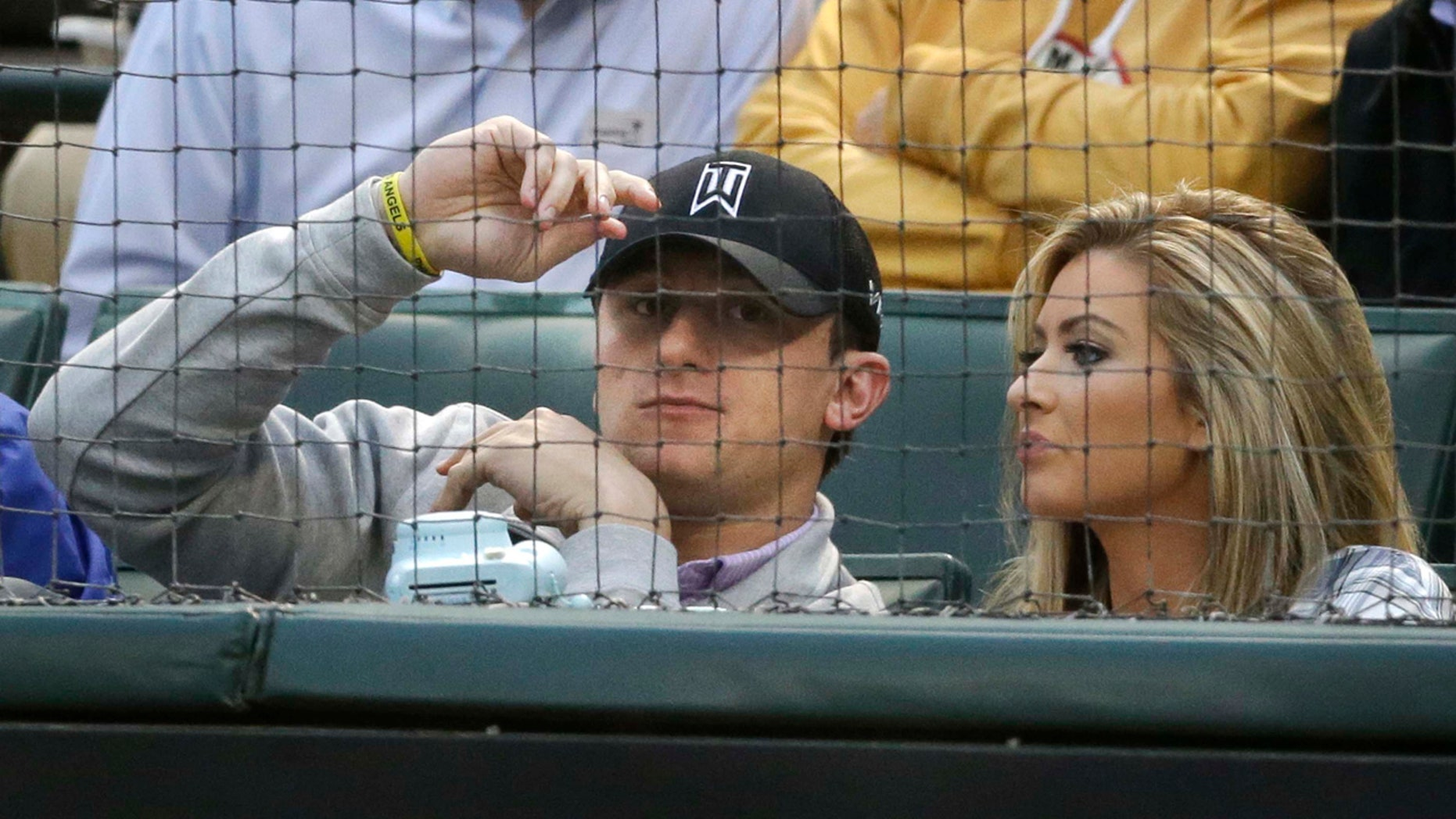 April 14, 2015: Johnny Manziel, left, sits with Colleen Crowley during a baseball game between the Los Angeles Angels and the Texas Rangers in Arlington, Texas. Dallas police announced Friday they were launching a criminal investigation into a domestic violence assault complaint filed against Manziel, who was involved in an altercation last weekend during which he allegedly struck Crowley several times. (AP Photo/LM Otero)