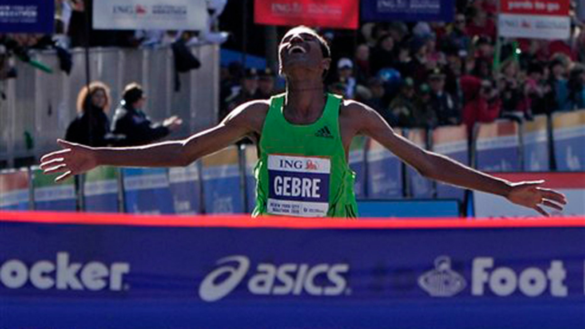 Gebre Gebrmariam, of Ethiopa, throws out his arms before breaking the tape to win the professional men's division at the New York City Marathon in New York, Sunday, Nov. 7, 2010.