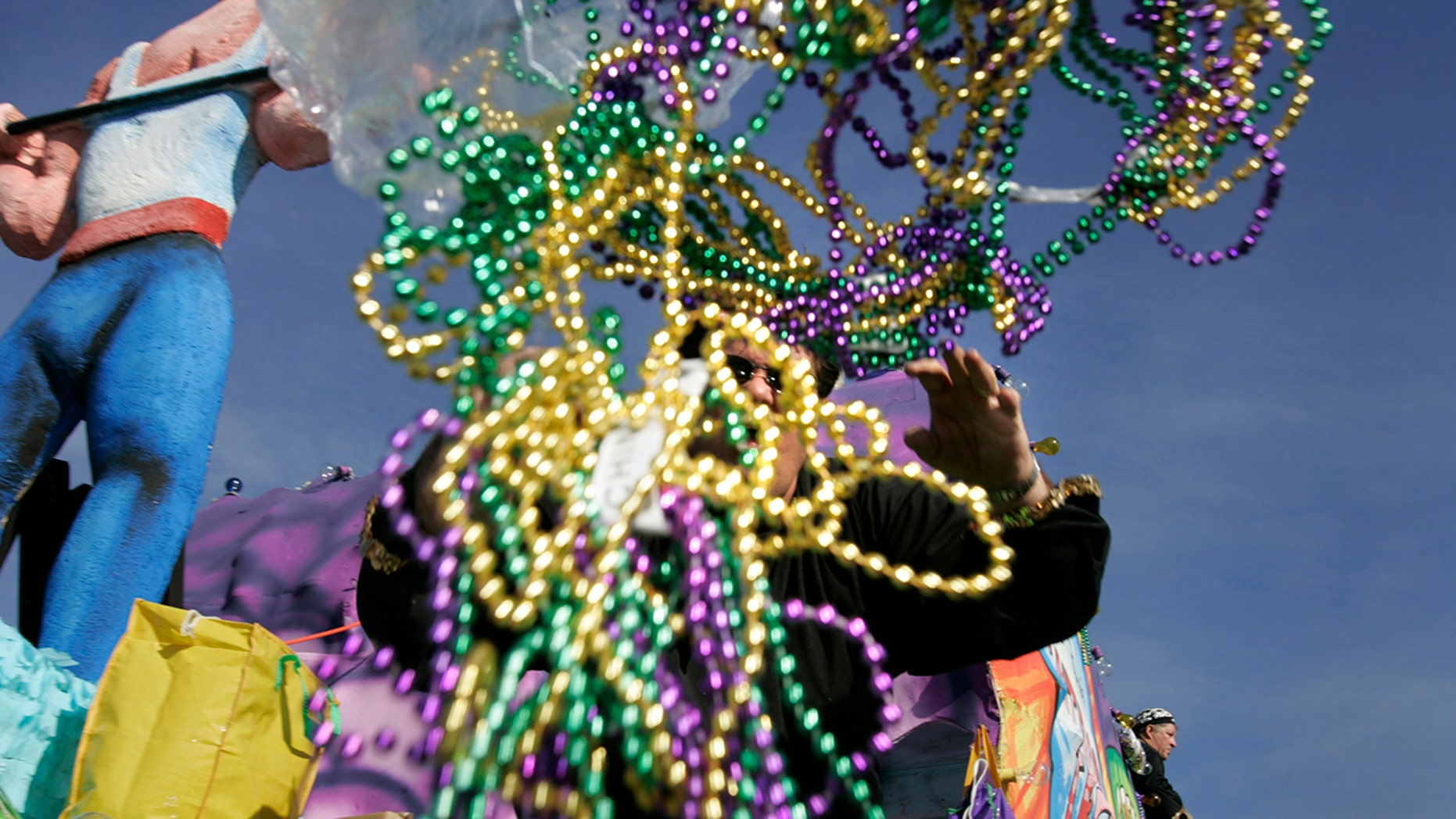 A parade rider throws out handfuls of beads during a Mardi Gras parade.
