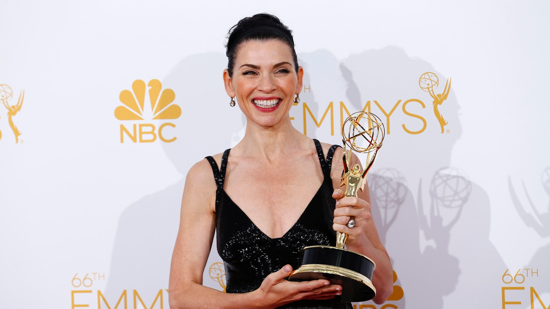"""Julianna Margulies poses backstage with her award for Outstanding Lead Actress in a Drama Series for the CBS series """"The Good Wife"""" at the 66th Primetime Emmy Awards in Los Angeles, California August 25, 2014.  REUTERS/Mike Blake (UNITED STATES -Tags: ENTERTAINMENT)(EMMYS-BACKSTAGE) - RTR43QQV"""