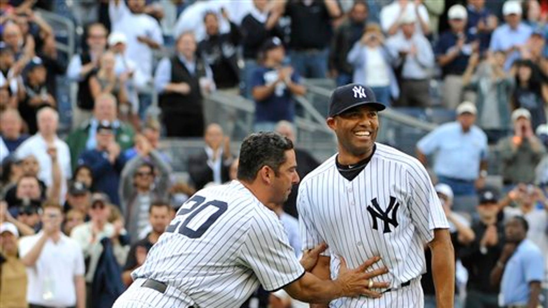 Sept 19: New York Yankees Jorge Posada pushes Mariano Rivera, right, back to the mound to acknowledge the cheers of the crowd after Rivera recorded his 602nd save as the Yankees beat the Minnesota Twins 6-4 on Monday, Sept. 19, 2011, at Yankee Stadium.