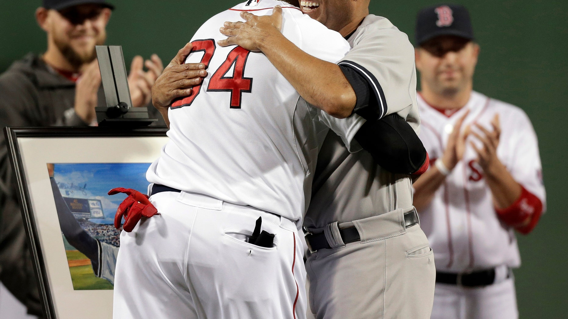 New York Yankees relief pitcher Mariano Rivera, right, hugs Boston Red Sox's David Ortiz during a tribute for Rivera before the start of a baseball game at Fenway Park, in Boston, Sunday, Sept. 15, 2013.