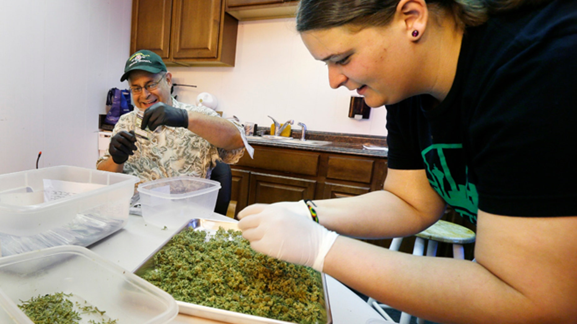 """July 1, 2014: In this photo, workers Kristi Tobias, right, and Bruce Cumming prepare packets of a variety of recreational marijuana named """"Space Needle"""" at Sea of Green Farms in Seattle. Workers at the grower, the first business licensed to grow recreational marijuana in Washington state, worked all weekend to have supplies ready for stores that were expected to be granted sale licenses on Monday, the day before the first day of legal recreational pot sales in Washington state."""