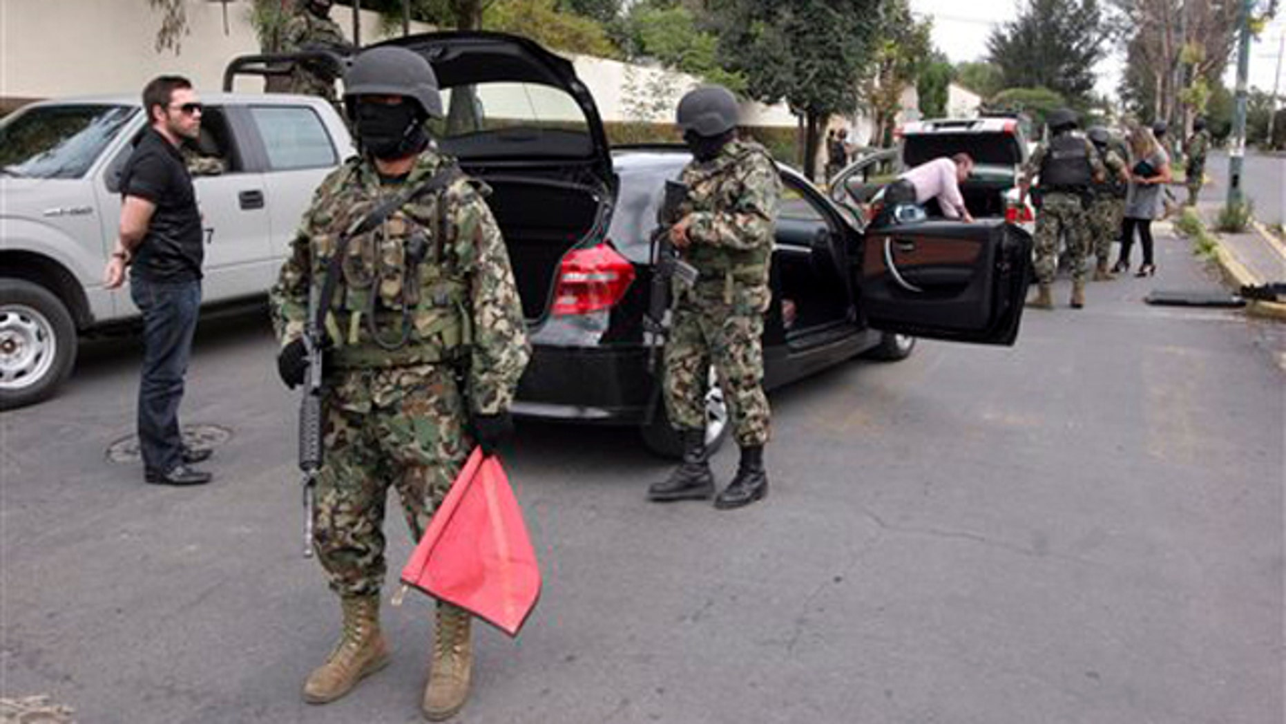 "Sept. 12, 2010: Navy marines guard a roadblock at the entrance to the residential compound where the alleged drug kingpin Sergio Villareal Barragan, alias ""El Grande,"" was arrested in Puebla, Mexico.  Mexican marines captured Villarreal, a presumed leader of the embattled Beltran Leyva cartel who appears on a list of the country's most-wanted fugitives, in a raid Sunday, the government said."