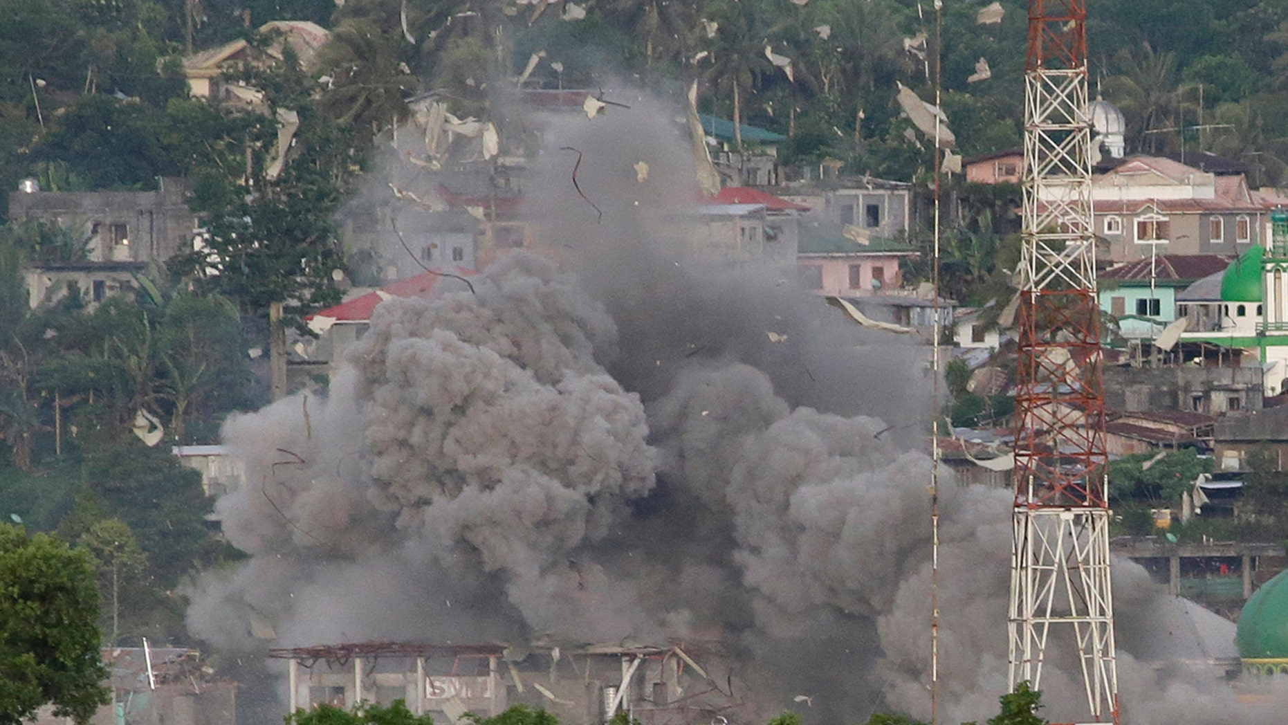Debris fly as Philippine Air Force fighter jets bomb suspected locations of Muslim militants as fighting continues in Marawi city, southern Philippines, Friday, June 9, 2017.