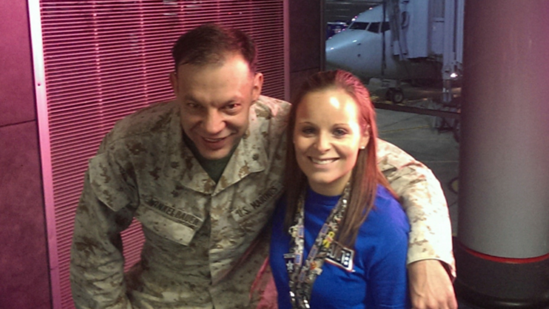 Nov. 4, 2013: Lindsy Wadas, director of the USO Center at Chicago's O'Hare International Airport, is shown with U.S. Marine Maj. Matthew Winkelbauer, left, after he and 13 other Marines arrived in Chicago before the final leg of their trip home to San Diego after a tour in Afghanistan.