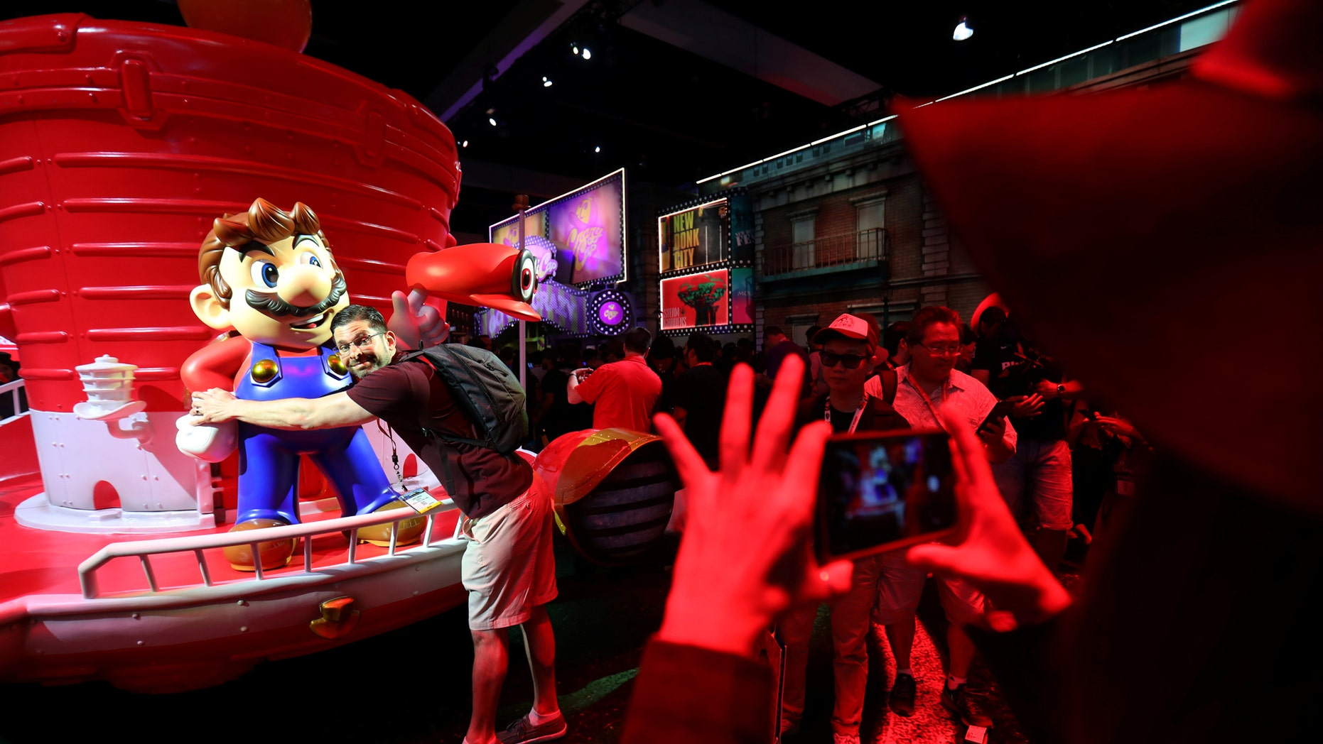 An attendee hugs a statue of Super Mario at the E3 2017 Electronic Entertainment Expo in Los Angeles, California, U.S. June 13, 2017. (REUTERS/ Mike Blake)