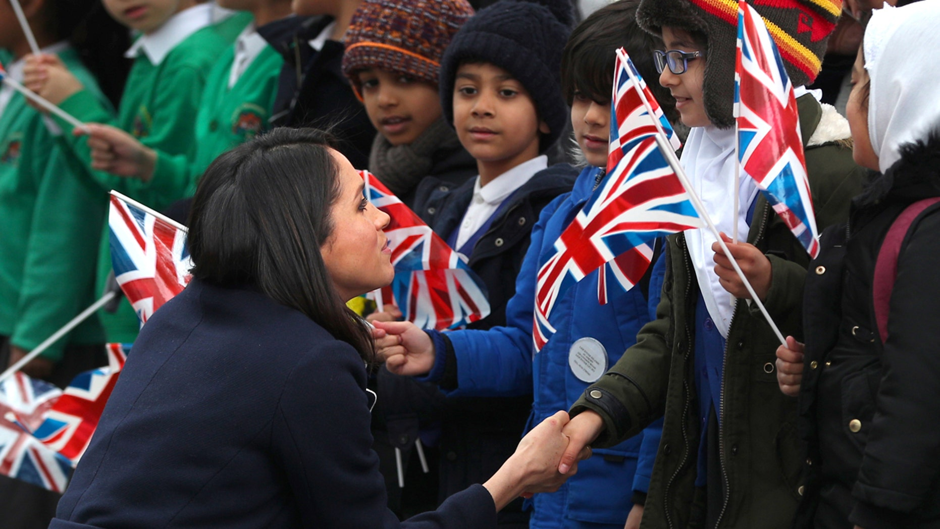 Meghan Markle talks to local school children during a walkabout with Britain's Prince Harry during a visit to Birmingham, Britain, March 8, 2018.