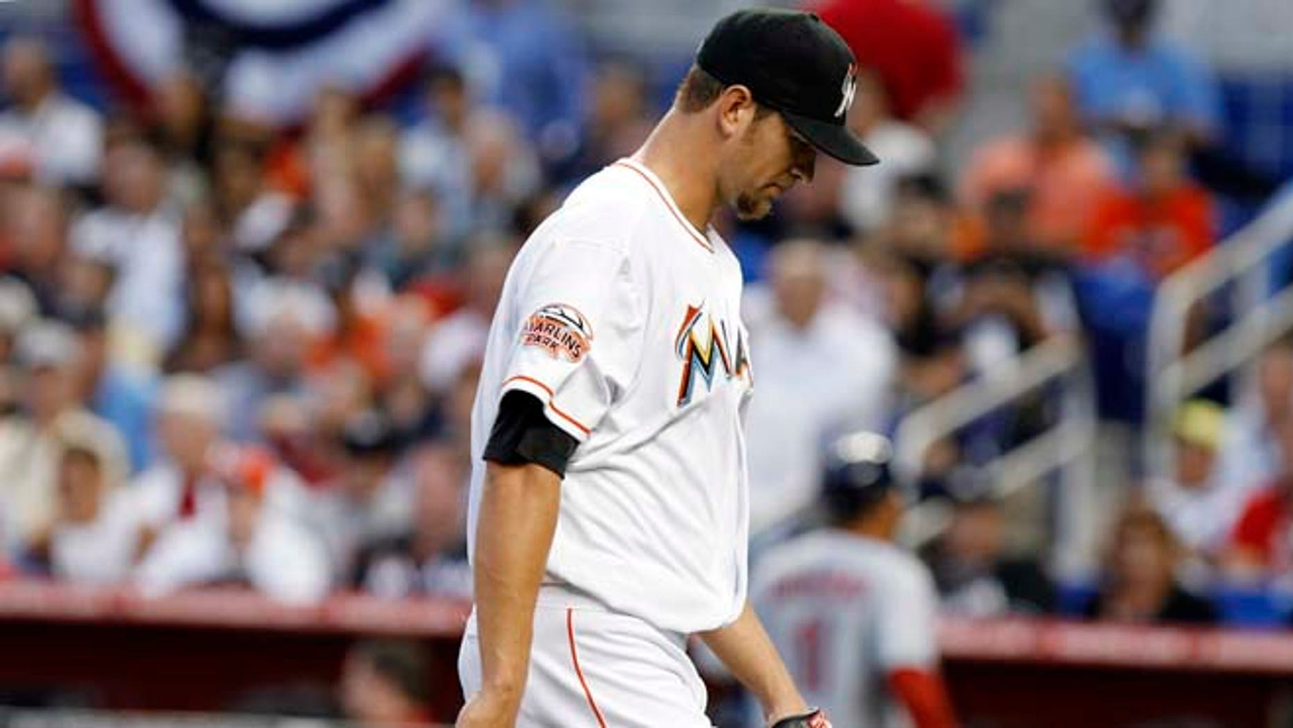 Miami Marlins starting pitcher Josh Johnson walks back to the dugout after giving up two runs to the St. Louis Cardinals in the first inning of the Opening Day baseball game, Wednesday, April 4, 2012, in Miami.