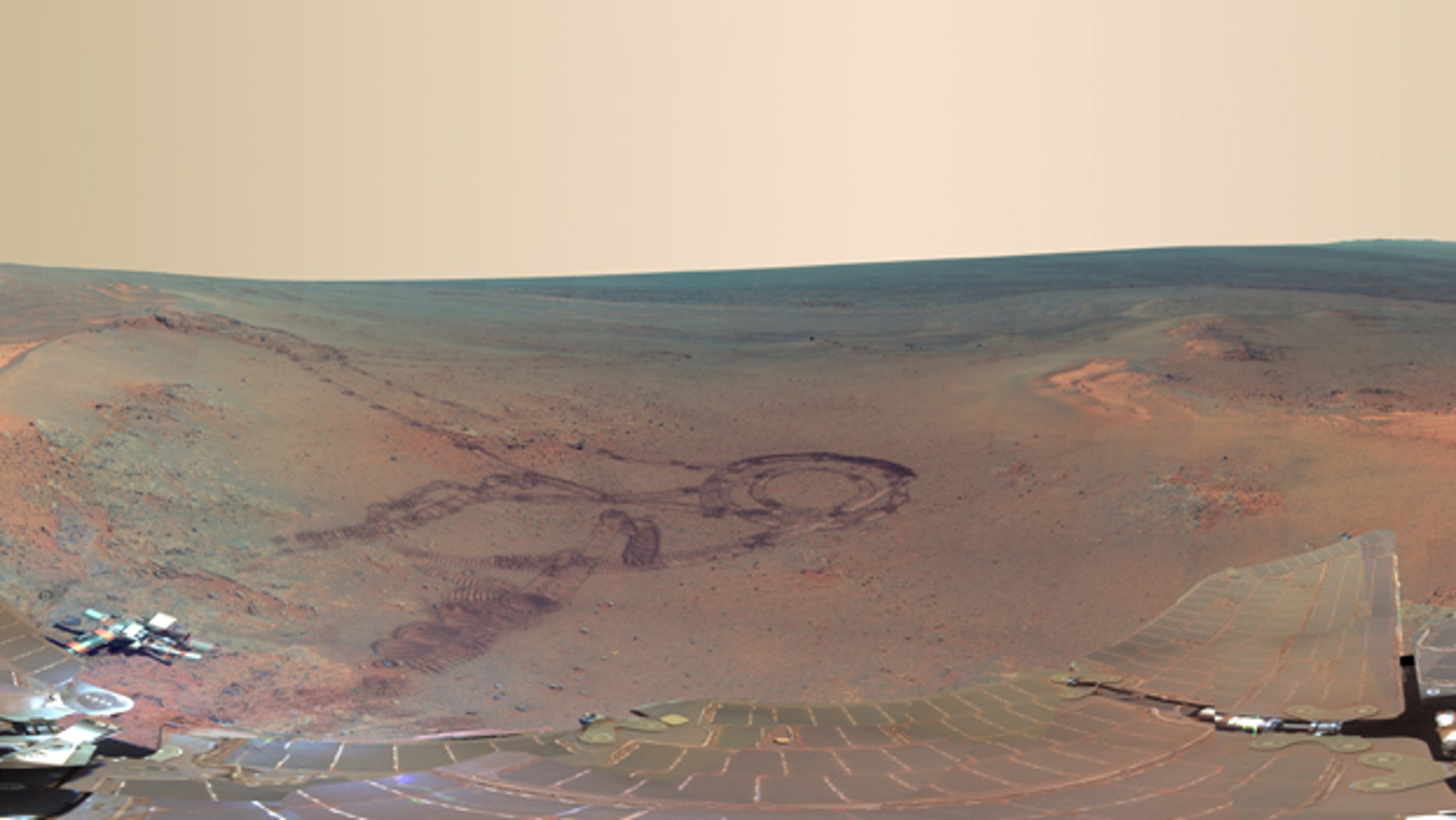 July 5, 2012: From fresh rover tracks to an impact crater blasted billions of years ago, a newly completed view from the panoramic camera (Pancam) on NASA's Mars Exploration Rover Opportunity shows the ruddy terrain around the outcrop where the long-lived explorer spent its most recent Martian winter.