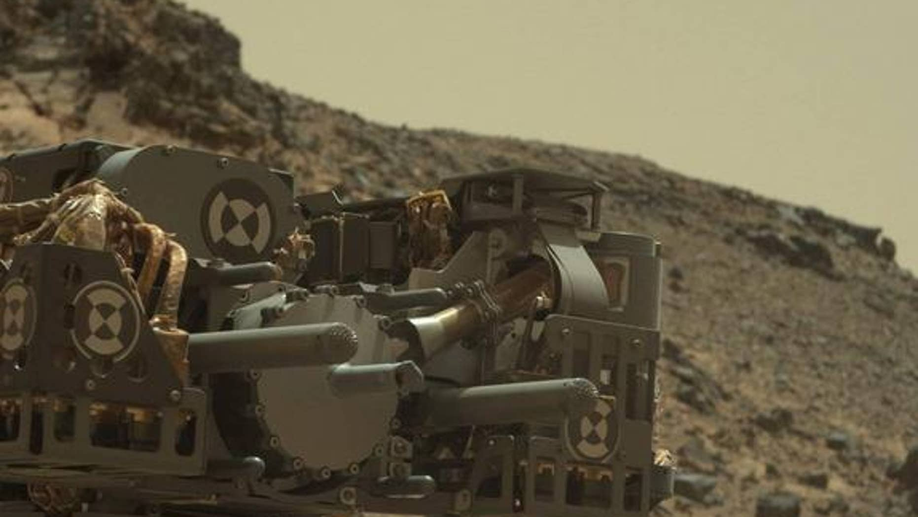 This raw-color image captured by the Mars rover Curiosity's Mastcam shows the robot's drill just after finishing a drilling operation at an outcrop called Telegraph Peak on Feb. 24, 2015.