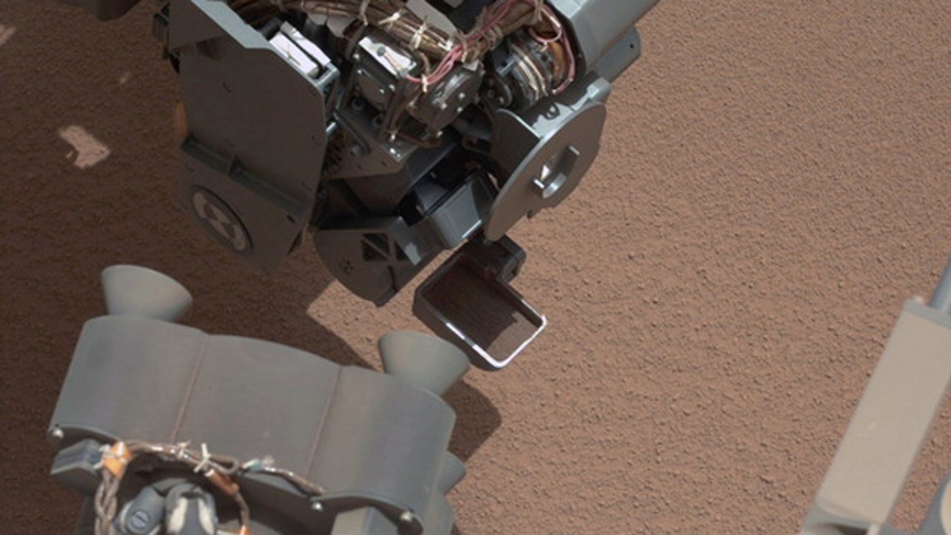 his image from the right Mast Camera (Mastcam) of NASA's Mars rover Curiosity shows a scoop full of sand and dust lifted by the rover's first use of the scoop on its robotic arm. In the foreground, near the bottom of the image, a bright object