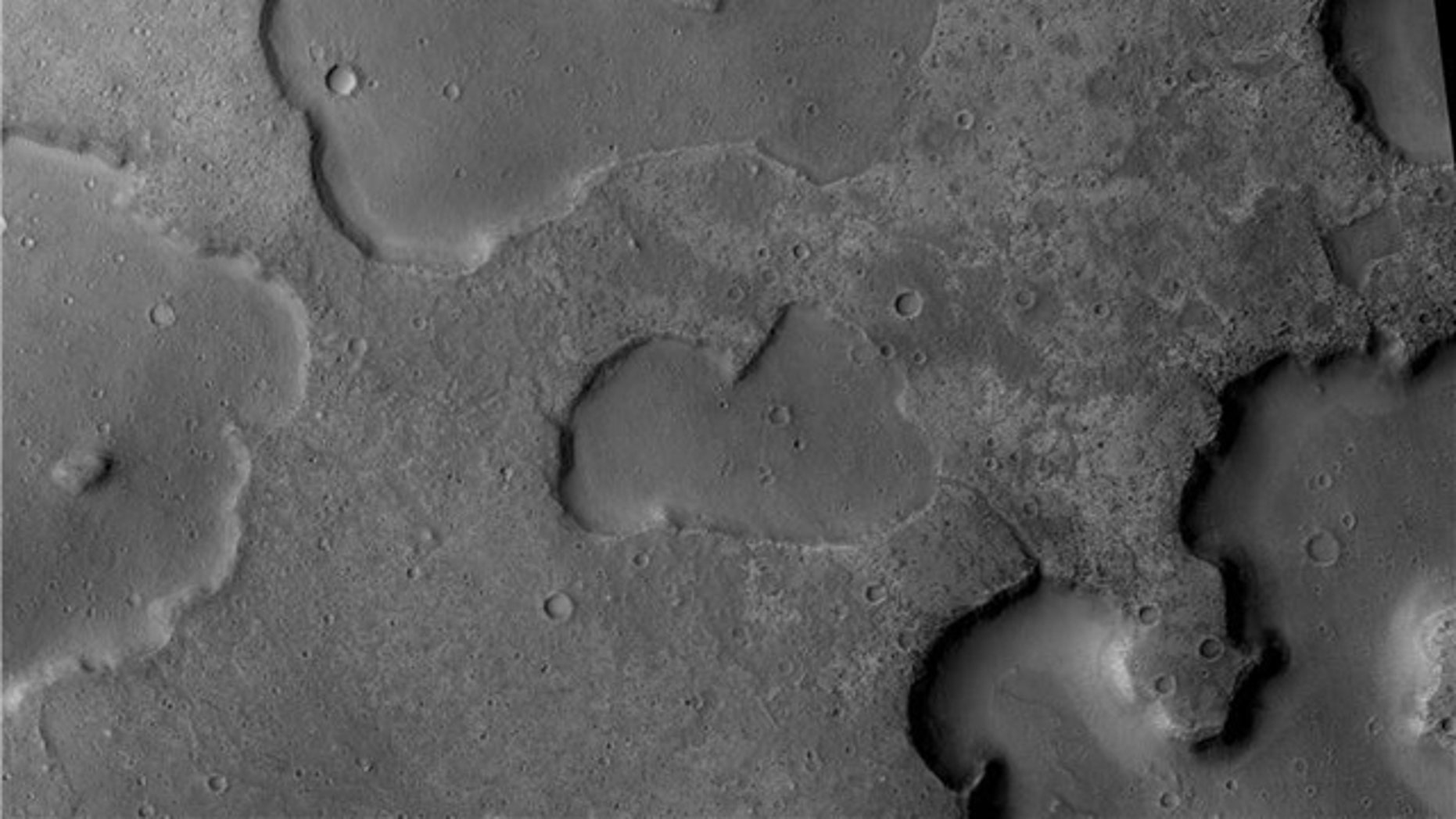The Mars Reconnaisance Orbiter's Context Camera captured channels running between depressions, evidence of ancient drainage between lakes, researchers say. The central depression is 4 km wide.
