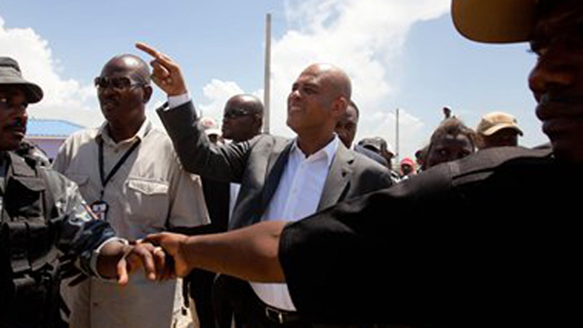In this photo taken Thursday July 21, 2011, a security detail forms a human barricade around Haiti's President Michel Martelly, center, during a tour of model homes in Port-au-Prince, Haiti.