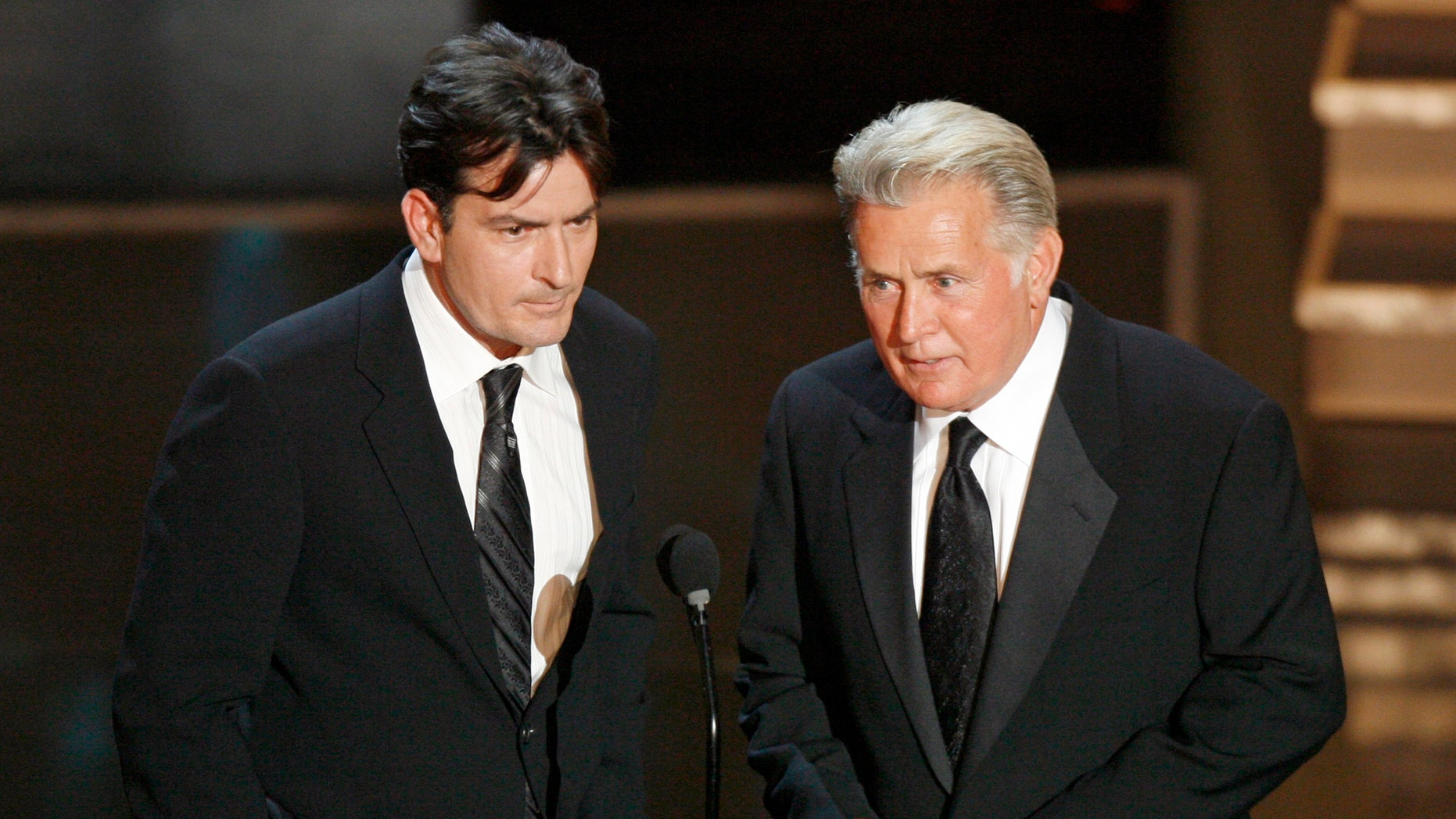 Charlie Sheen, left, and his father Martin Sheen present the best supporting actress in a miniseries or movie award during the 58th annual Primetime Emmy Awards at the Shrine Auditorium in Los Angeles August 27, 2006.  REUTERS