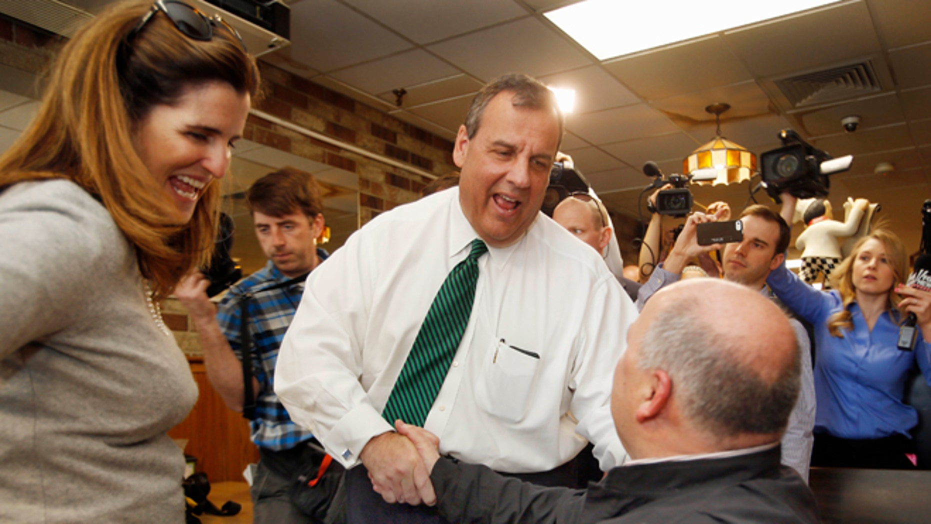 April 14, 2015: New Jersey Gov. Chris Christie, R-N.J. , accompanied by his wife Mary Pat, shakes hands with Don VanDenBerghe during a stop in New Hampshire.