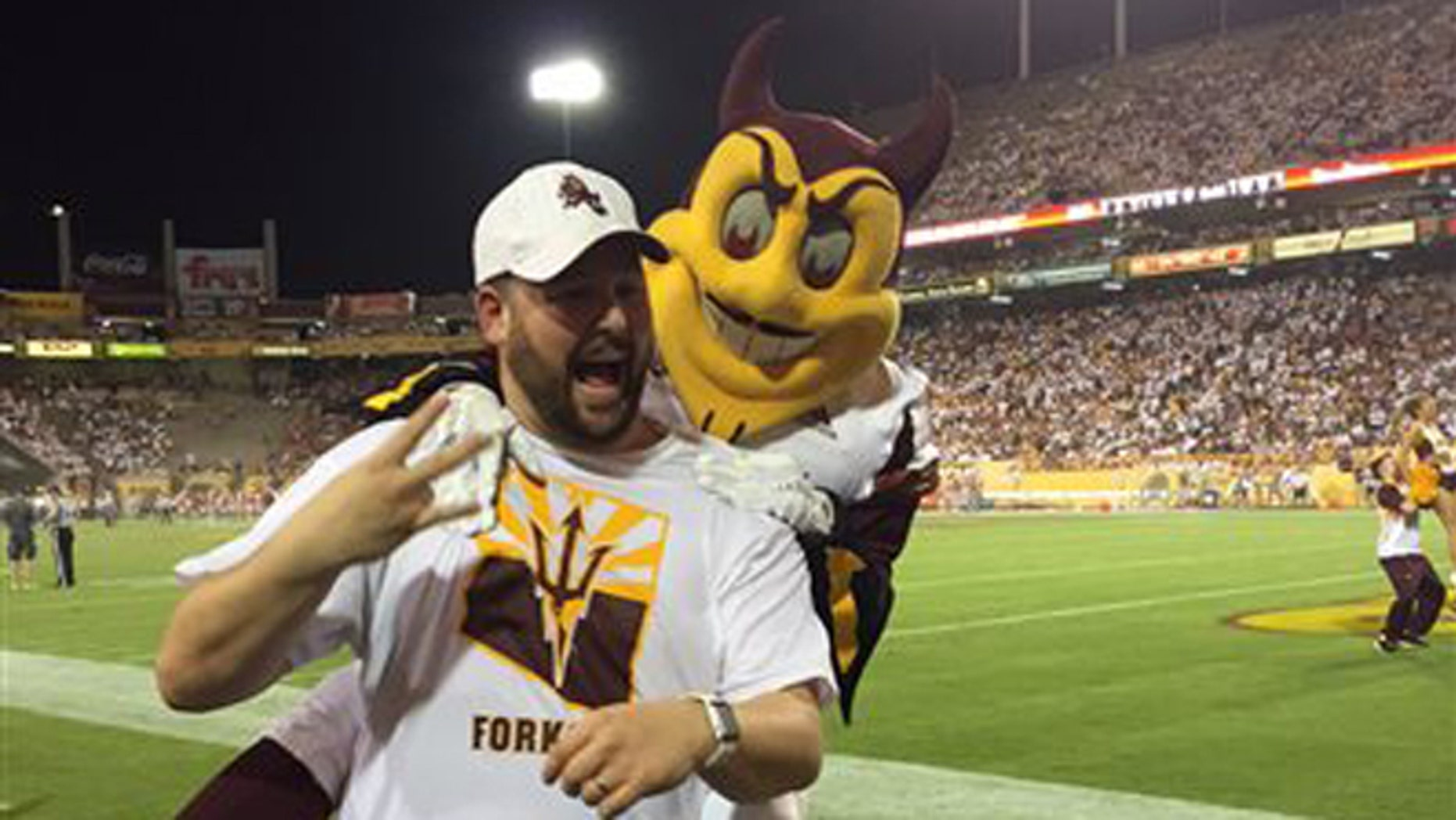 Sept. 18, 2015: This photo courtesy of David Schapira shows ASUs mascot Sparky jumping on David Schapira at a Arizona State University football game in Tempe, Ariz. Schapira, a Tempe City Councilman, has filed a claim against Arizona State University for injuries suffered when the school mascot leapt on him.