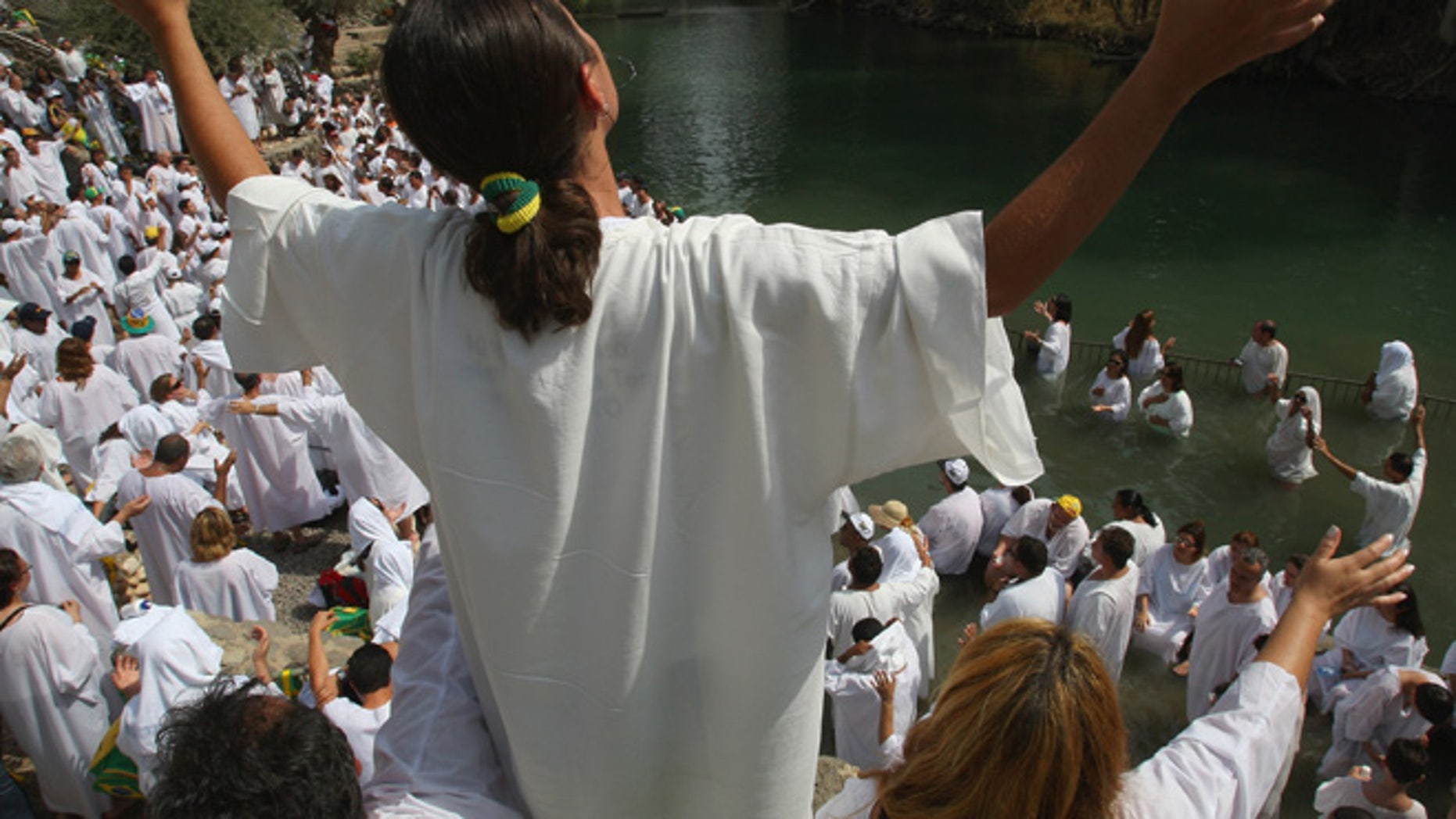 YARDENIT, ISRAEL - OCTOBER 01:  Brazilian Evangelist Christians raise their arms in prayer during their mass baptism ceremony in the Jordan River on October 1, 2007 at Yardenit in northern Israel. The group of 700 worshippers descended in the biblical river as part of their pilgrimage to the Holy Land.  (Photo by David Silverman/Getty Images)