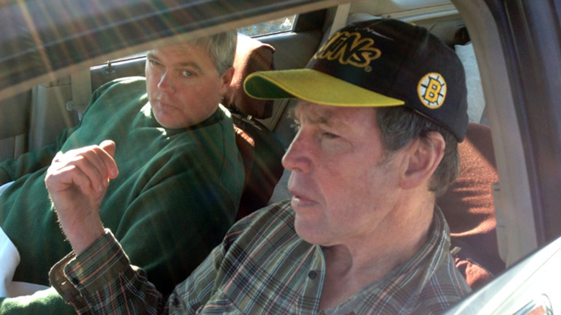 In this photo made Saturday, Oct. 19, 2013, Fred Schaeffer, left, of Raymond, N.H. and George Reynolds, right, of Derry, N.H. sit in a car after being rescued in waters off of Salem, Mass. The two New Hampshire men whose boat capsized off the Massachusetts coast prayed and sang gospel songs as they survived a 15-hour ordeal that ended with them being rescued by a passing fishing boat. The men spent Friday night sitting on a plank over two hulls of a 25-foot trimaran as waves crashed over them through the night.