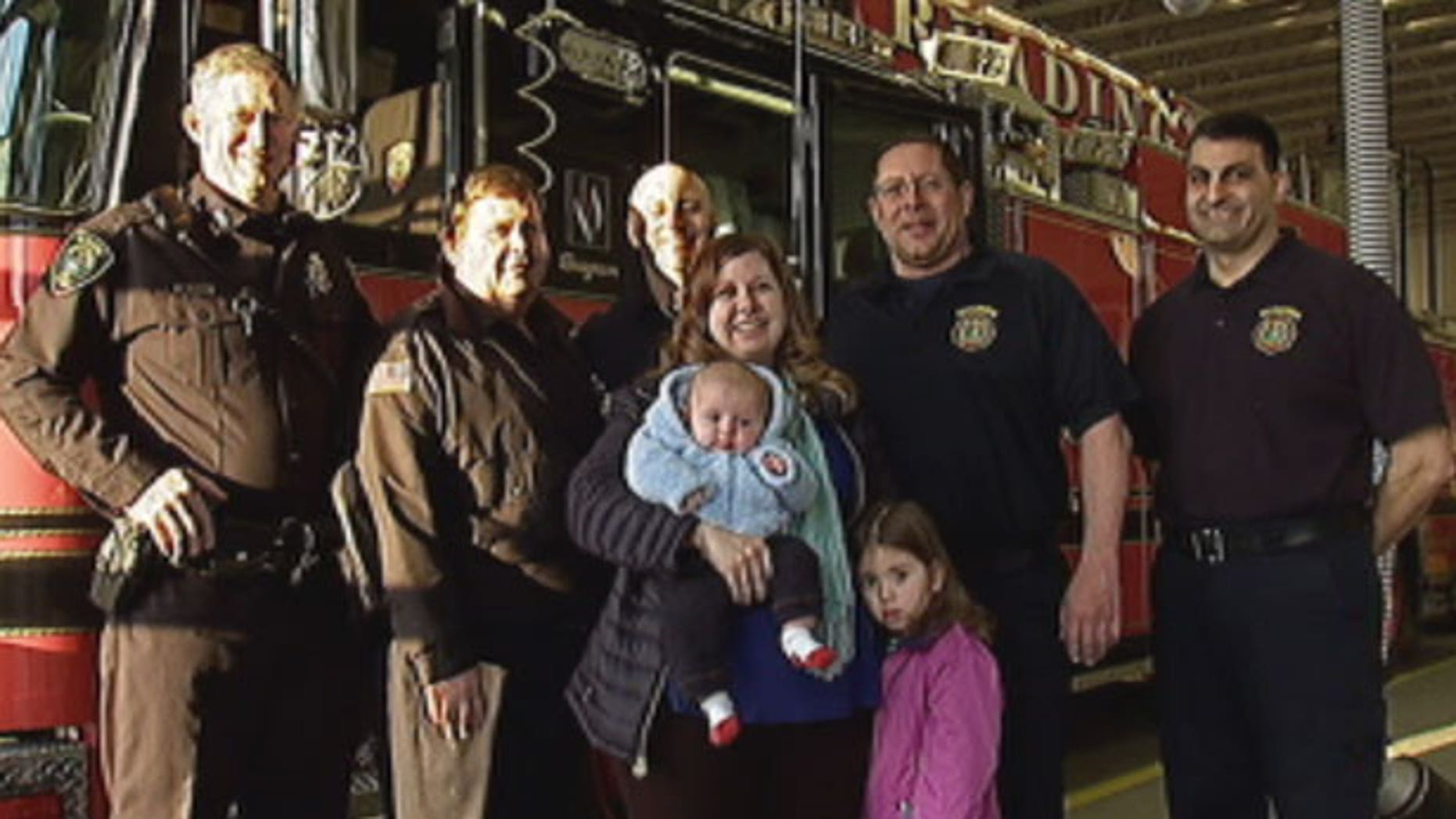 This photo shows Massachusetts firefighters and the family they rescued from a jammed elevator.