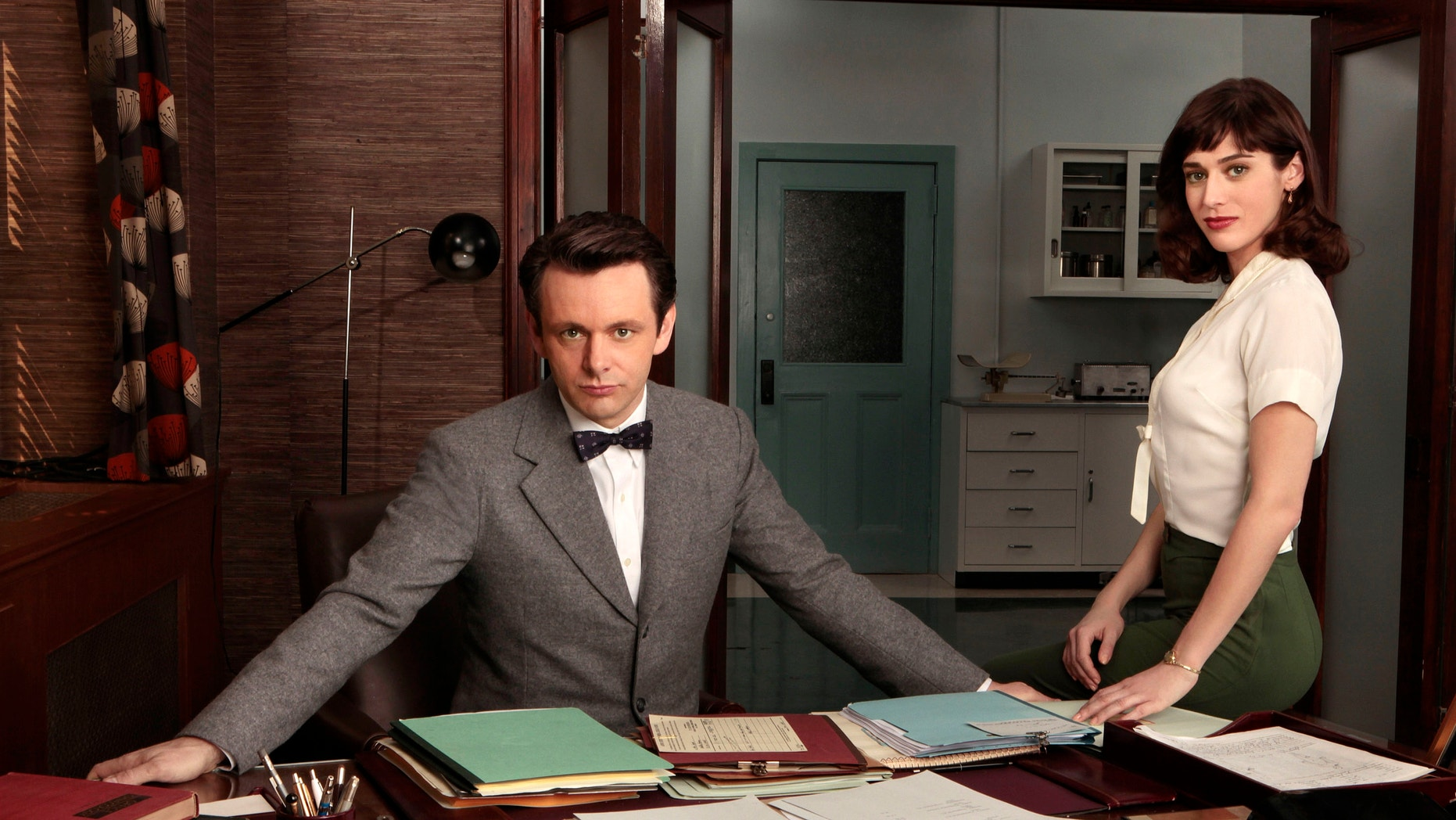 """This publicity image released by Showtime shows Michael Sheen as Dr. William Masters, left, and Lizzy Caplan as Virginia Johnson from """"Masters of Sex."""""""