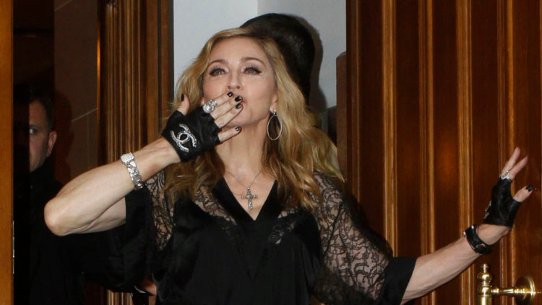U.S. singer Madonna sends an air kiss to her fans as she walks out of a building during the opening of a new fitness club on the eve of her MDNA tour concert at the Olympic sports complex in Moscow, August 6, 2012. REUTERS/Ivan Burnyashev (RUSSIA - Tags: ENTERTAINMENT) - RTR36B32