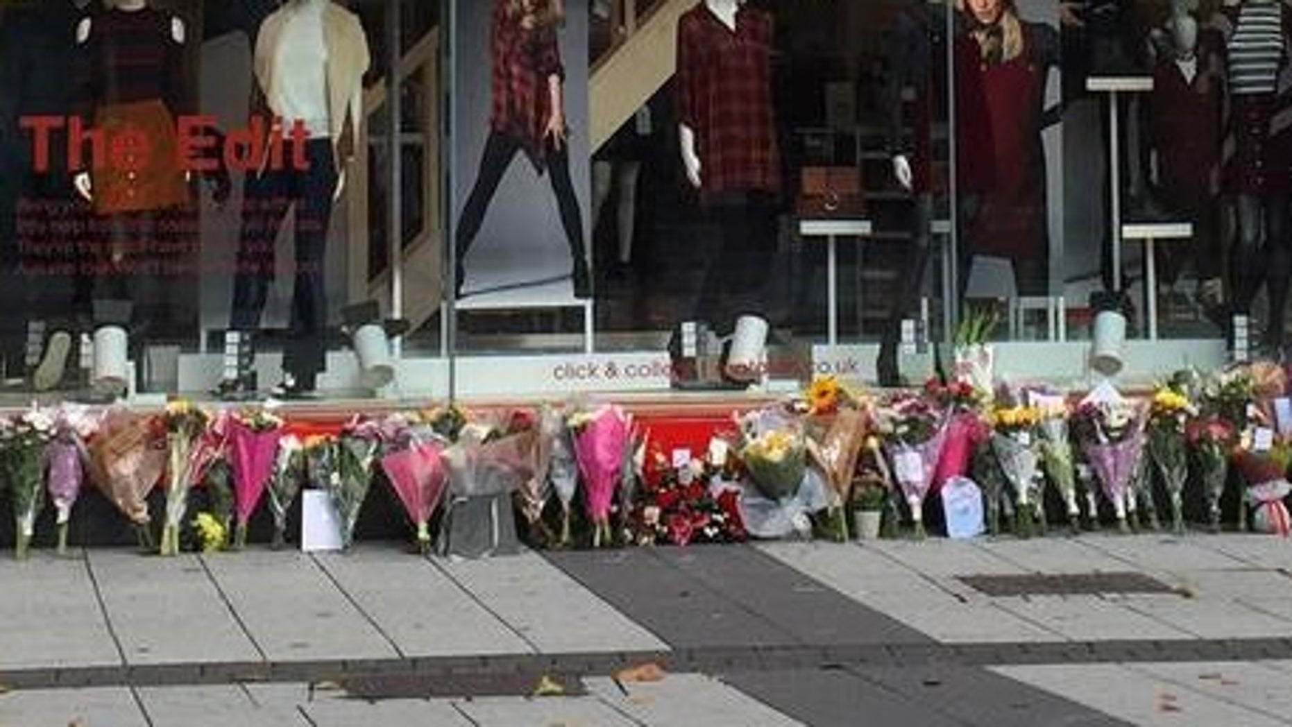 Flowers left outside the store where the couple worked, after the murders last September.