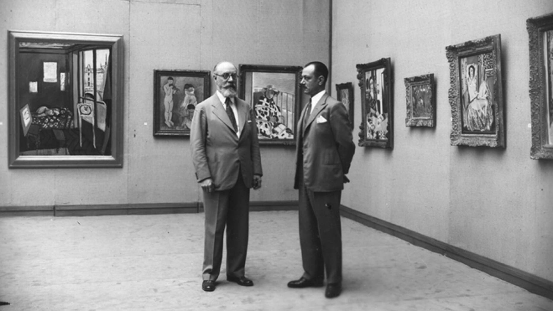 1931:  The French painter Henri Matisse (1869 - 1954) (left) at an exhibition of his work at the Galerie Georges Petit, Paris. The exhibition was organised by the collector Etienne Bignou (right).  (Photo by Hulton Archive/Getty Images)
