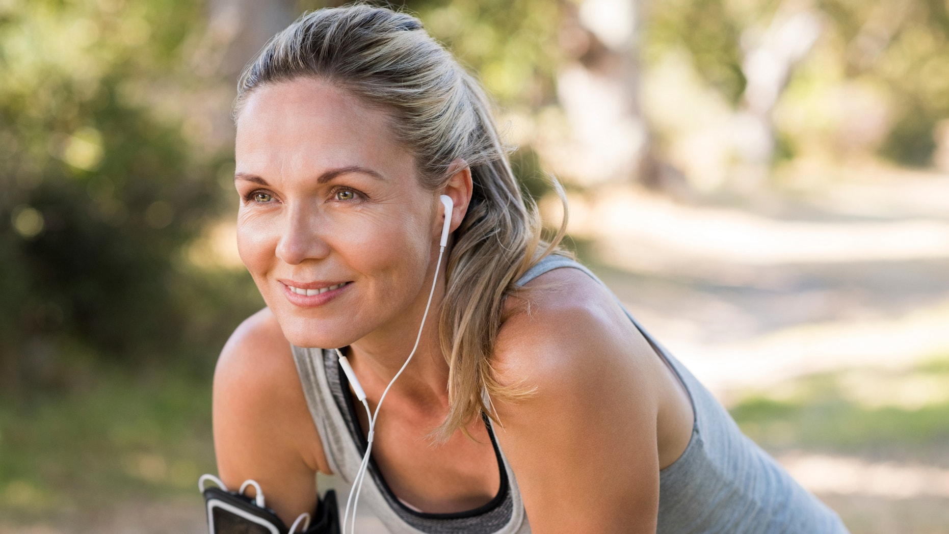 Portrait of athletic mature woman resting after jogging. Beautiful senior blonde woman running at the park on a sunny day. Female runner listening to music while jogging.