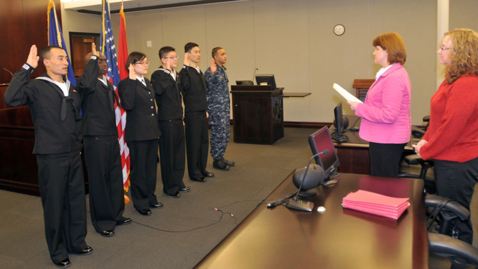 The first Navy Sailors to participate in the Secretary of Defense's Military Accessions Vital to National Interest pilot program are issued the oath of citizenship by Stacey Summers, branch chief from the U.S. Citizenship and Immigration Services Chicago field office in 2010.