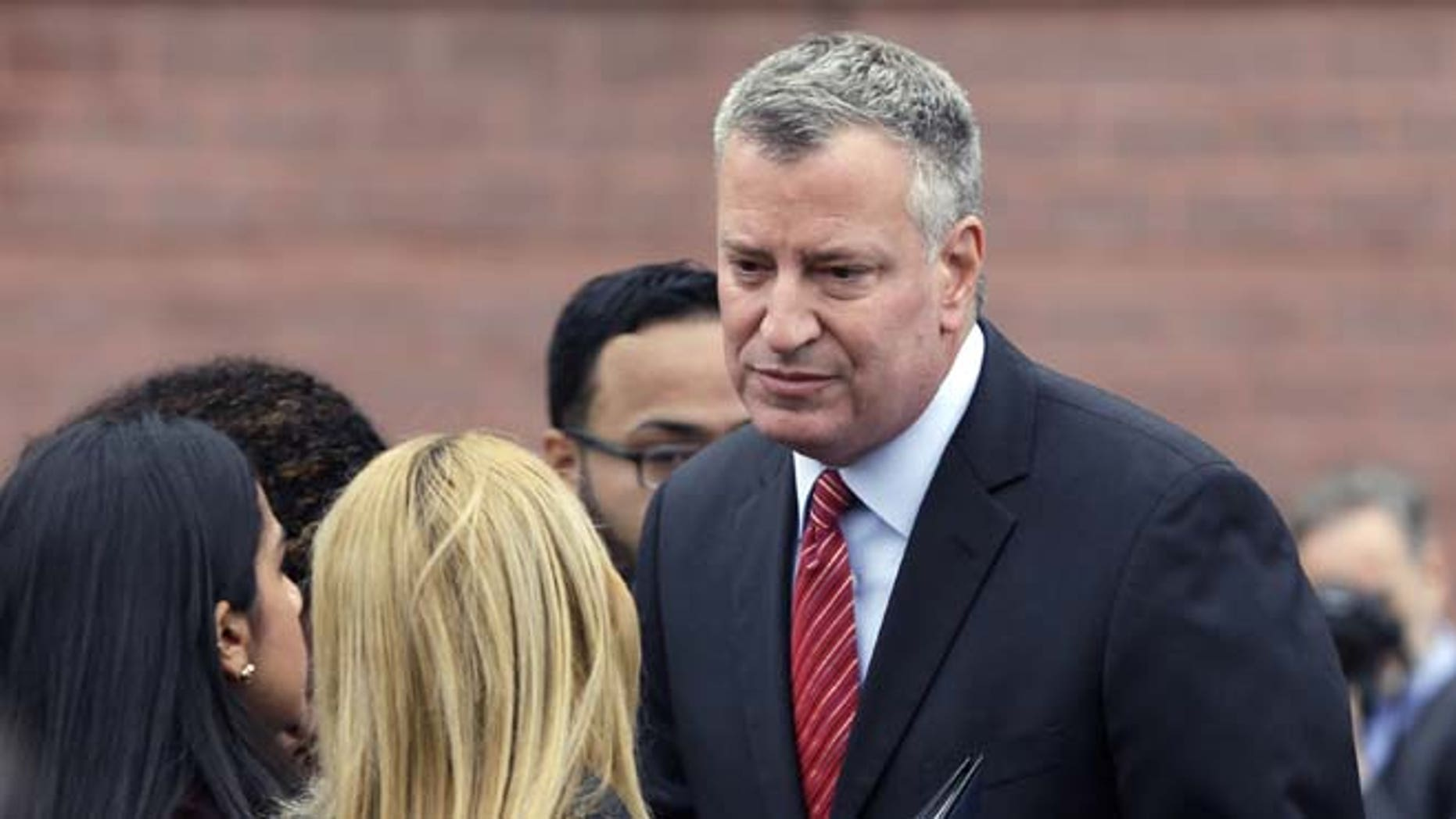 In this Wednesday, Nov. 12, 2014 photo New York City Mayor Bill de Blasio greets family members at the Flight 587 Memorial in the Rockaways section in New York.