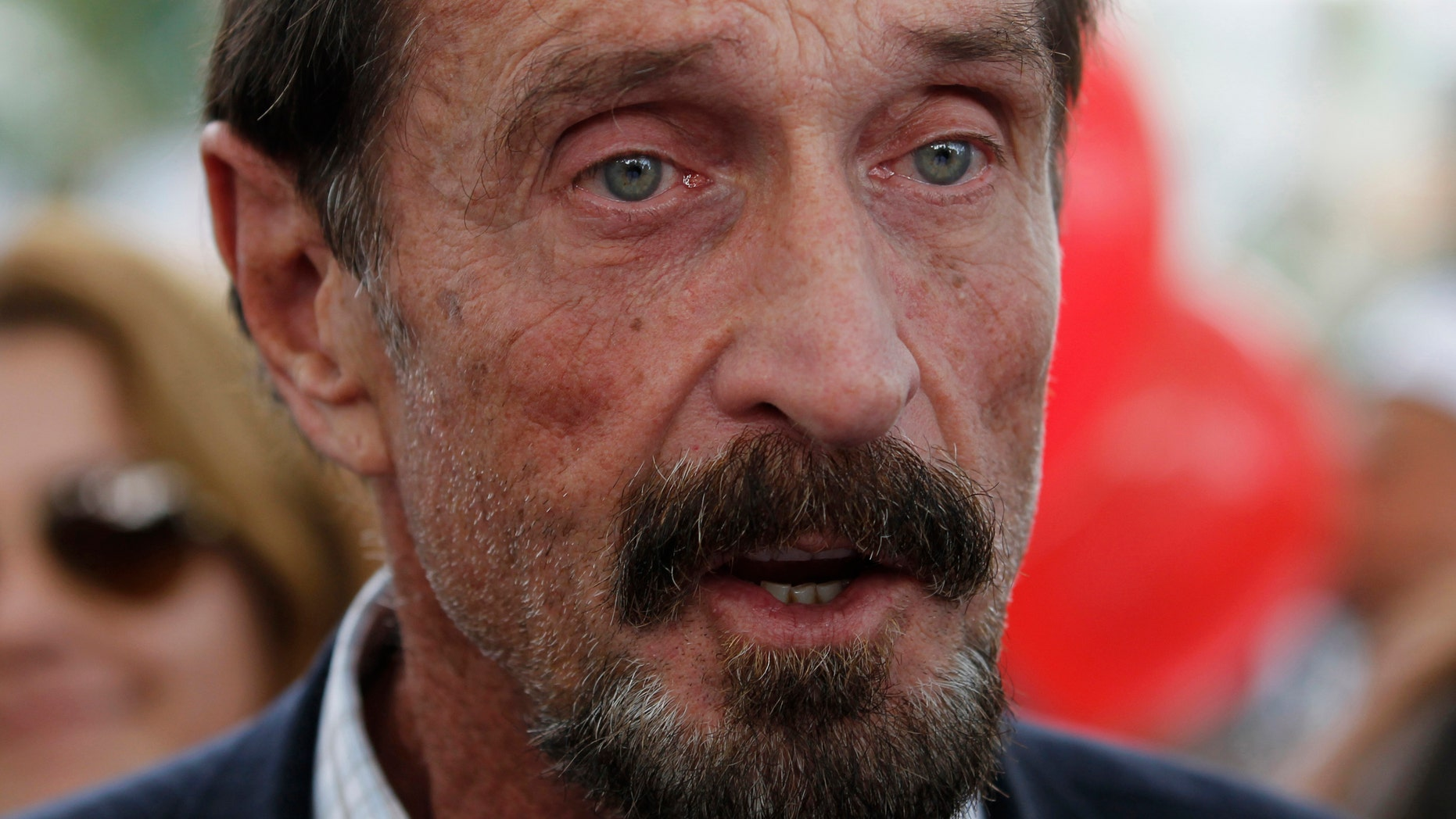 File photo. Computer software pioneer John McAfee speaks with reporters outside his hotel in Miami Beach, Florida December 13, 2012.