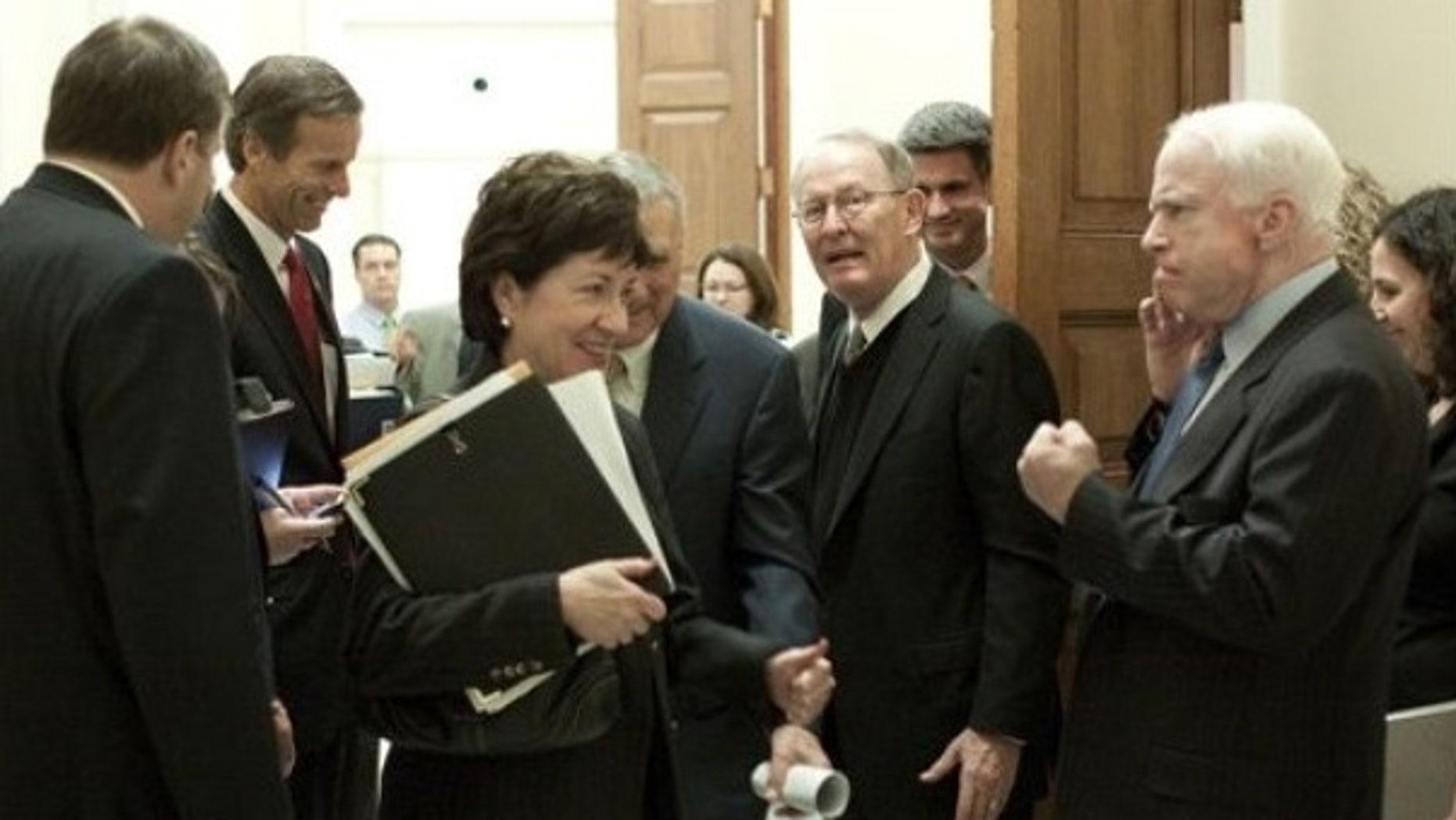 Dec. 9: Sen. John McCain plays rough with Maine Republican Sen. Susan Collins after a GOP meeting (AP).