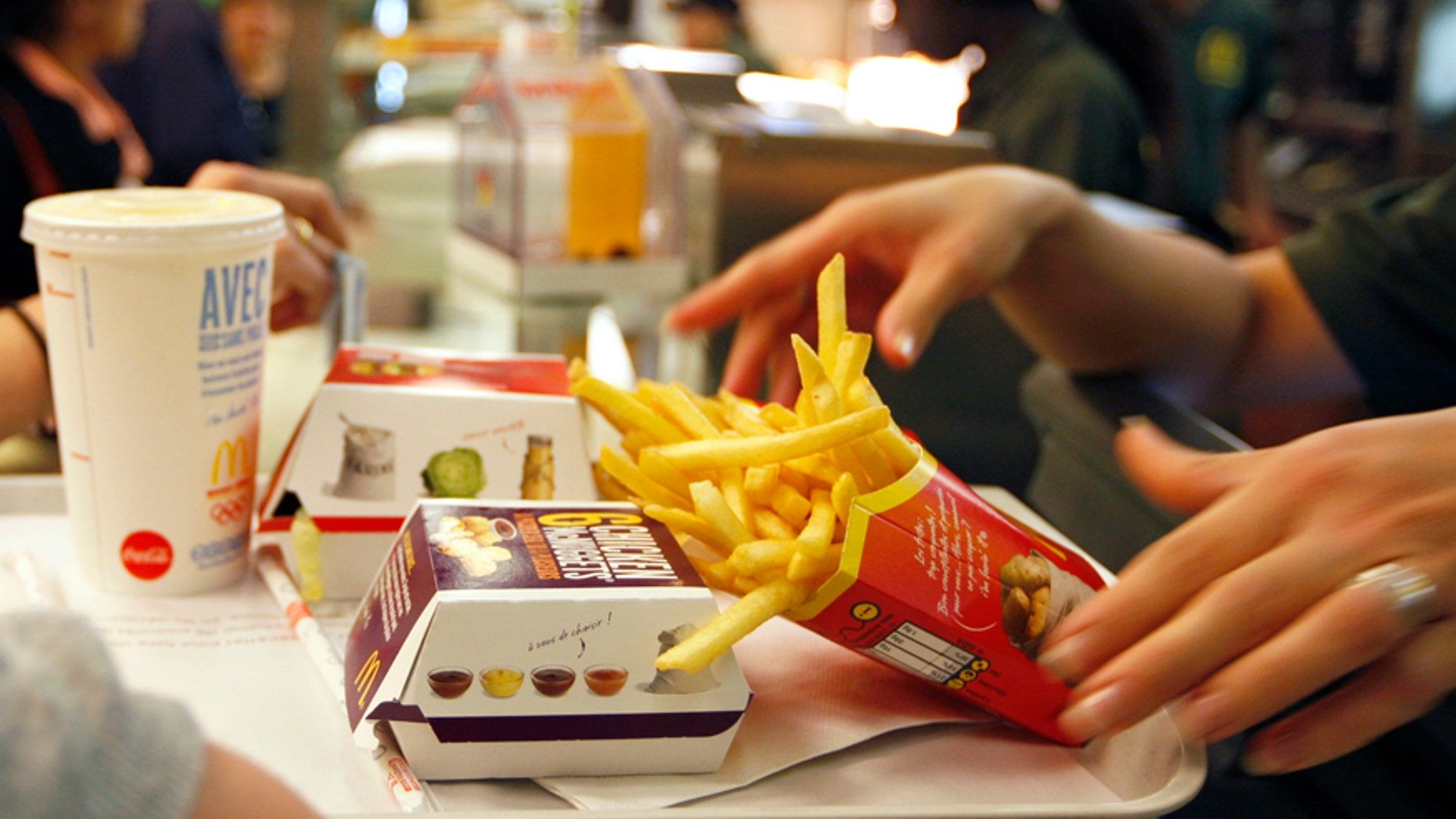 An employee at a McDonald's restaurant serves lunches to customers in Strasbourg, France.